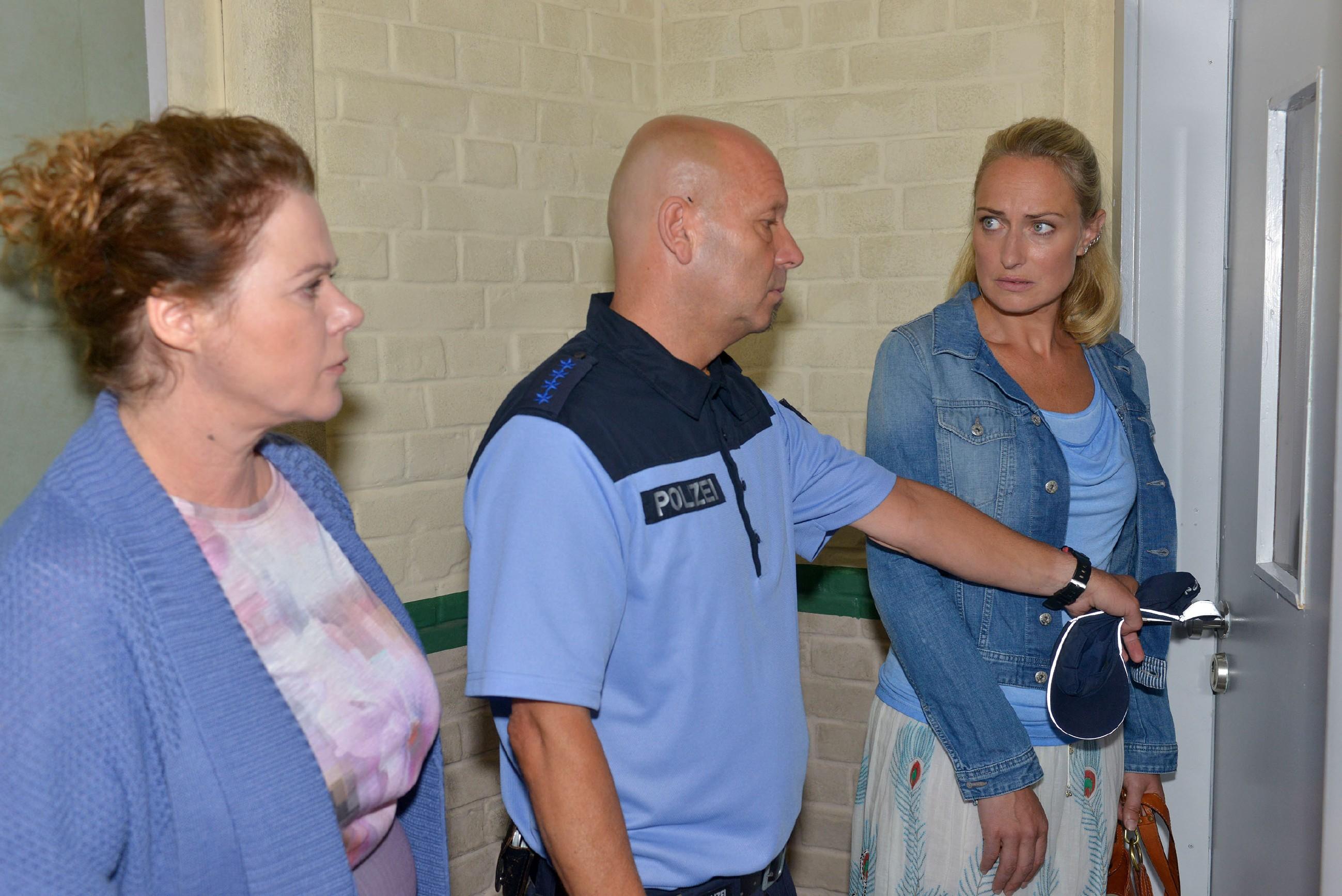 In Begleitung eines Polizisten (Komparse) appellieren Bärbel Butz (Verena Berger, l.) von der Ausländerbehörde und Maren (Eva Mona Rodekirchen) an Lilly, die Wohnungstür zu öffnen... (Quelle: © RTL / Rolf Baumgartner)