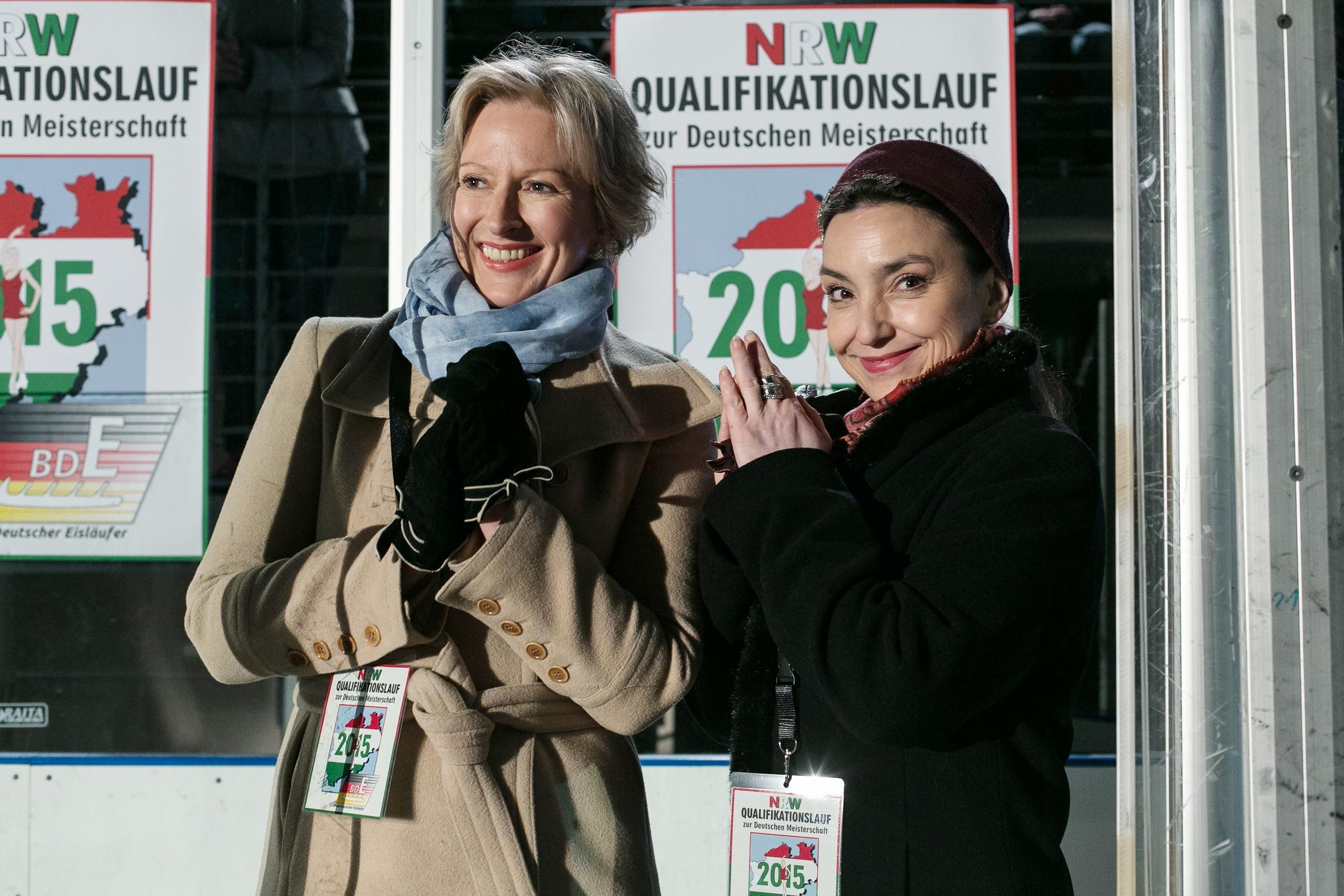 Trainerin Caroline (Olivia Augustinski, l.) und Simone (Tatjana Clasing) sehen eine fehlerfreie Kür von Marie auf dem Eis und applaudieren. (Quelle: RTL / Kai Schulz)