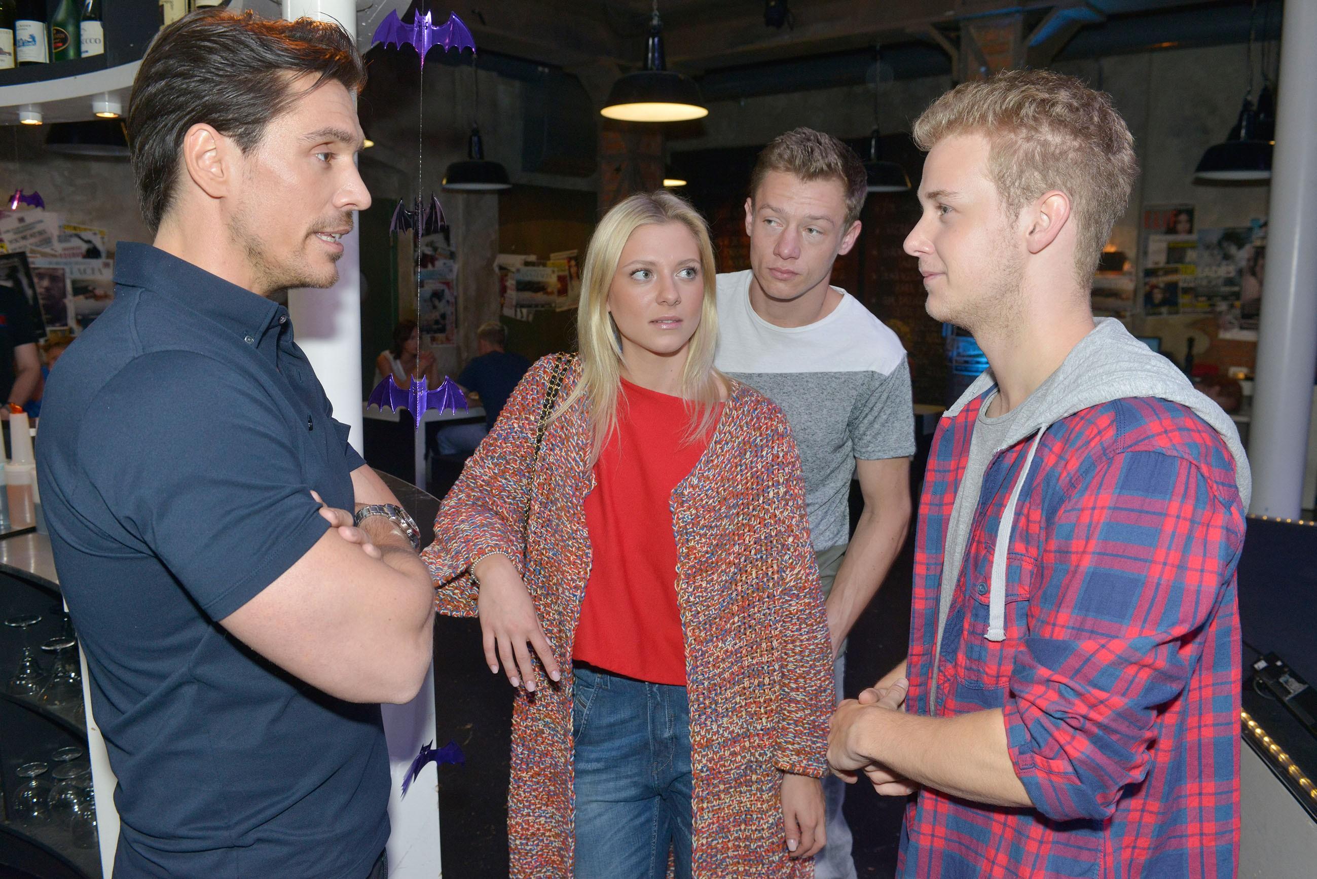 Im Beisein von Sunny (Valentina Pahde) und Vince (Vincent Krüger, 2.v.r.) erhält Jonas (Felix van Deventer, r.) von David (Philipp Christopher) eine demütigende Abfuhr, als er um eine Chance als DJ im Mauerwerk bittet.