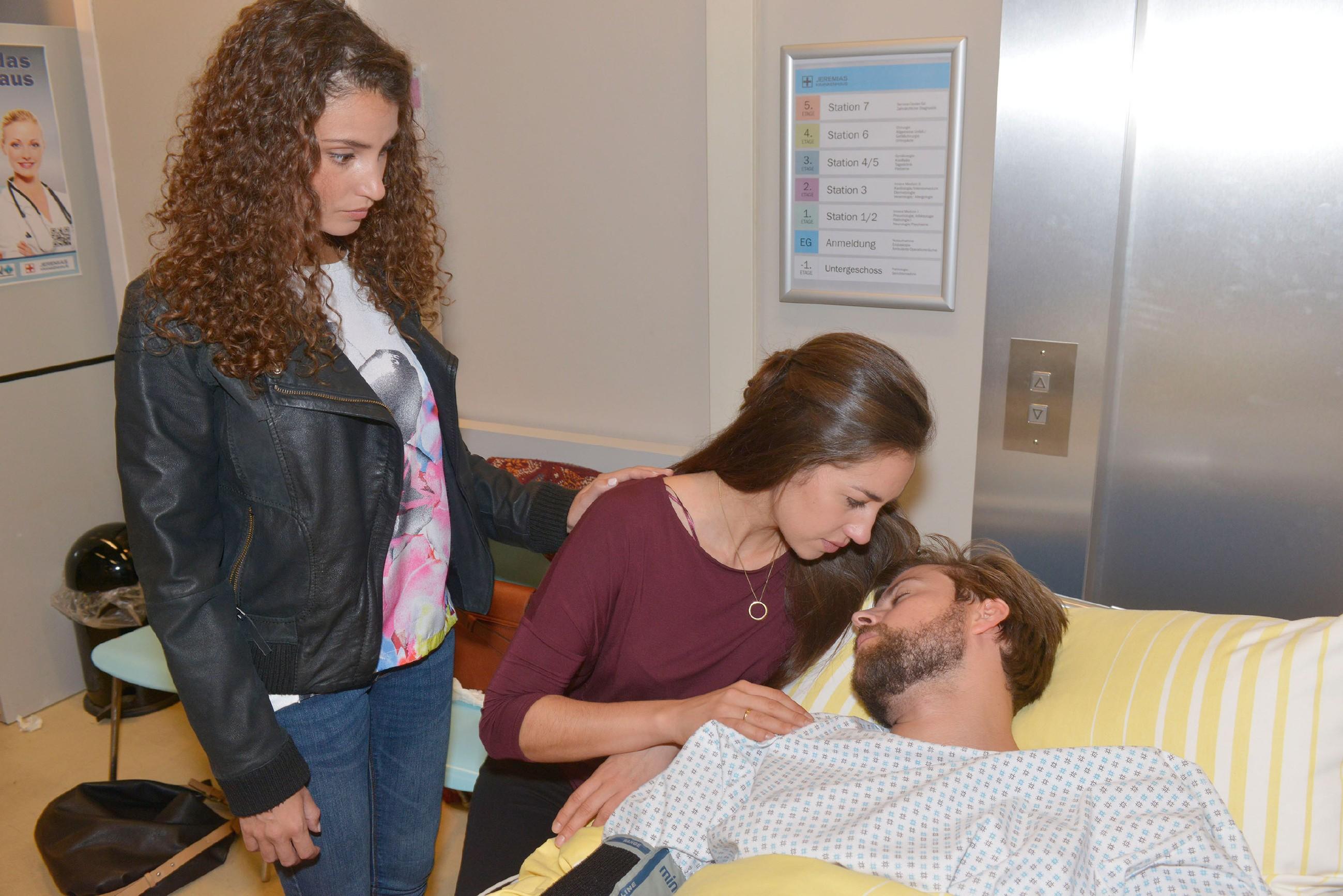Ayla (Nadine Menz, l.) und besonders Elena (Elena Garcia Gerlach) sorgen sich um John (Felix von Jascheroff), der mit einer eitrige Rippenfellentzündung ins Krankenhaus gebracht wurde. (Quelle: RTL / Rolf Baumgartner)