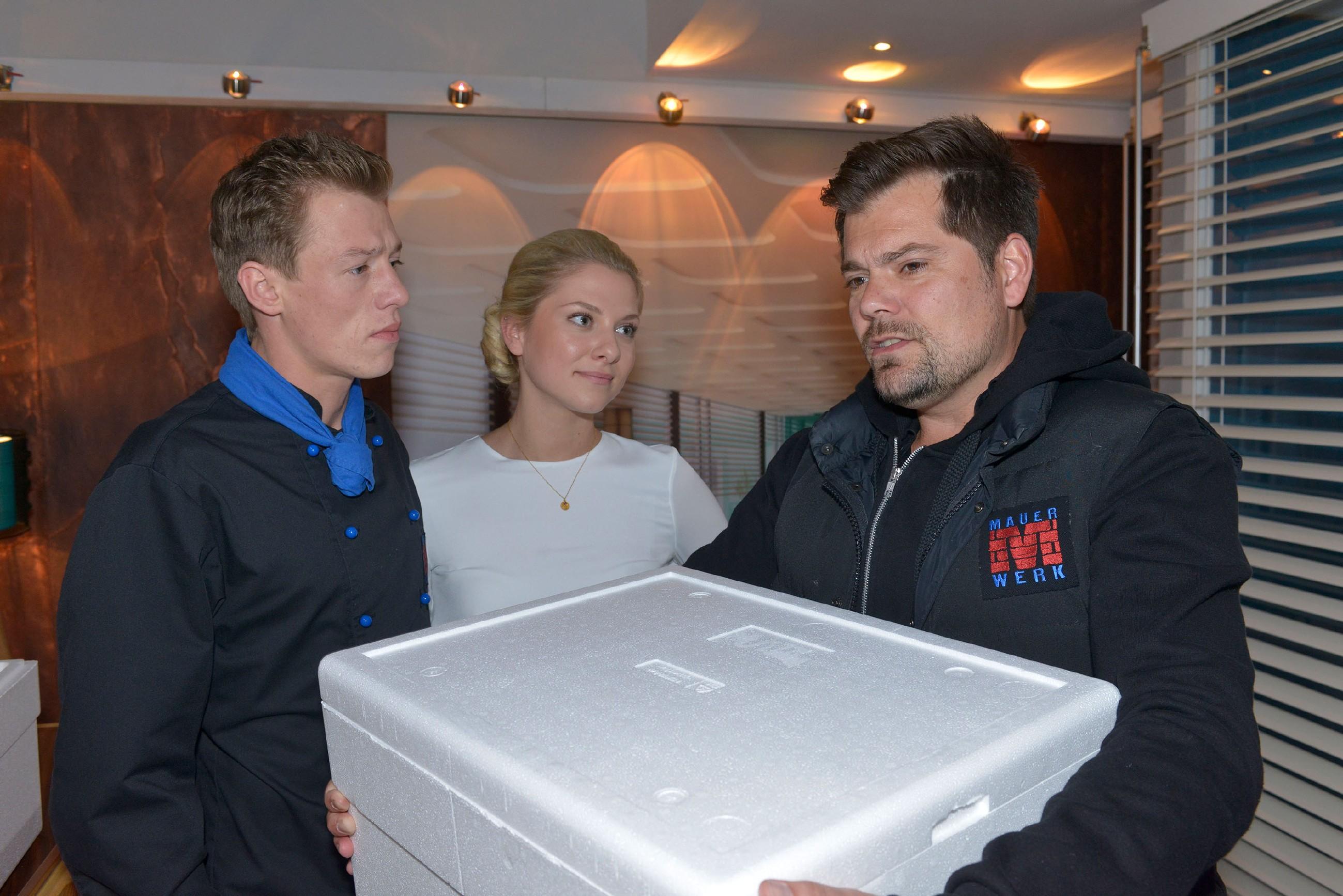 Vince (Vincent Krüger, l.) gerät unter Druck, als Leon (Daniel Fehlow) ihm im Beisein von Sunny (Valentina Pahde) die Verantwortung für die Eröffnung der Immobilienfirma überträgt.