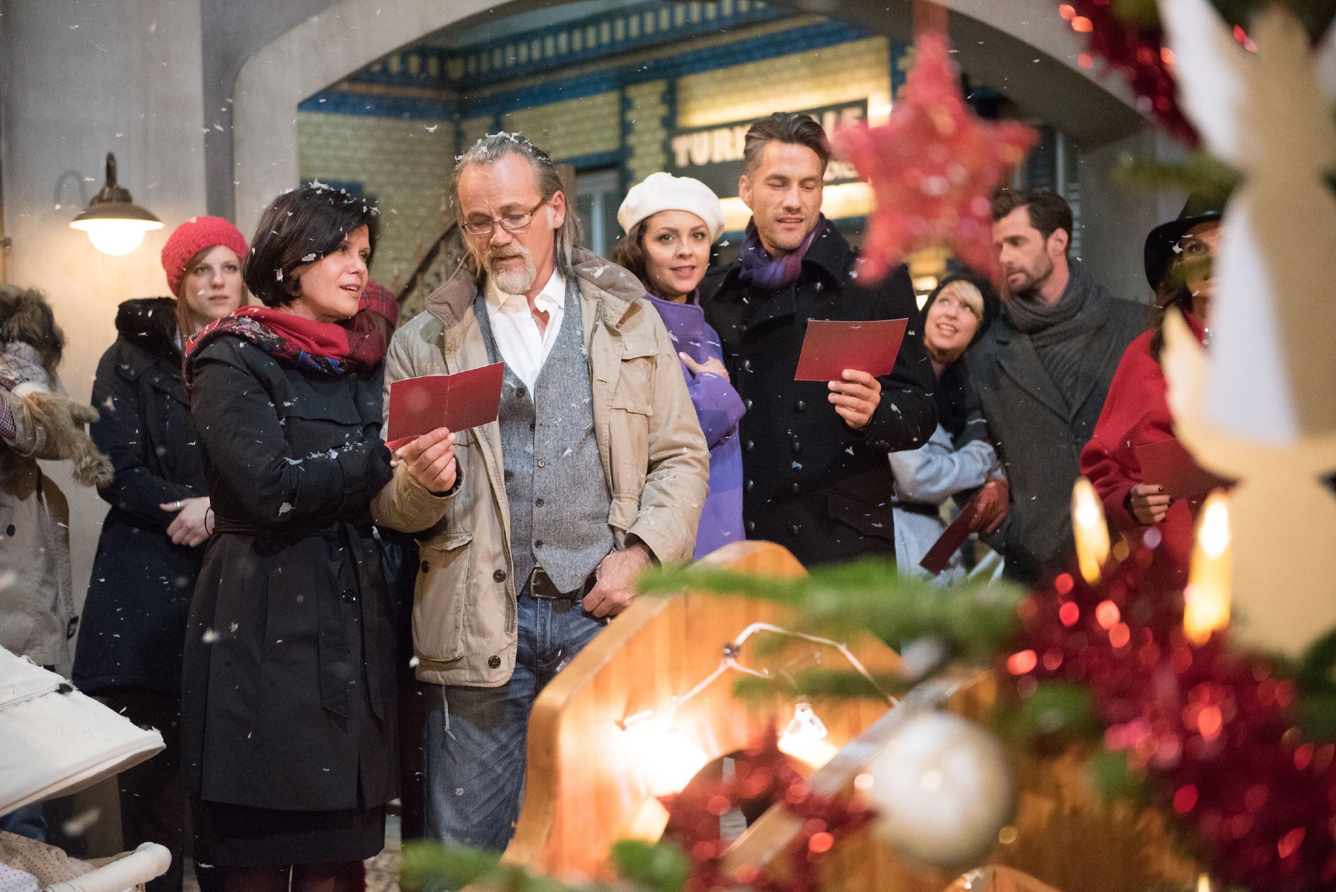Traditionell haben sich die Bewohner der Schillerallee, (v.l.) Elli (Nora Koppen), Irene (Petra Blossey), Robert (Luca Maric), Caro (Ines Kurenbach), Malte (Stefan Bockelmann), Ute (Isabell Hertel), Henning (Benjamin Kiss) und Britta (Tabea Heynig), im Innenhof zum gemeinsamen Singen eingefunden. (Quelle: RTL / Stefan Behrens)