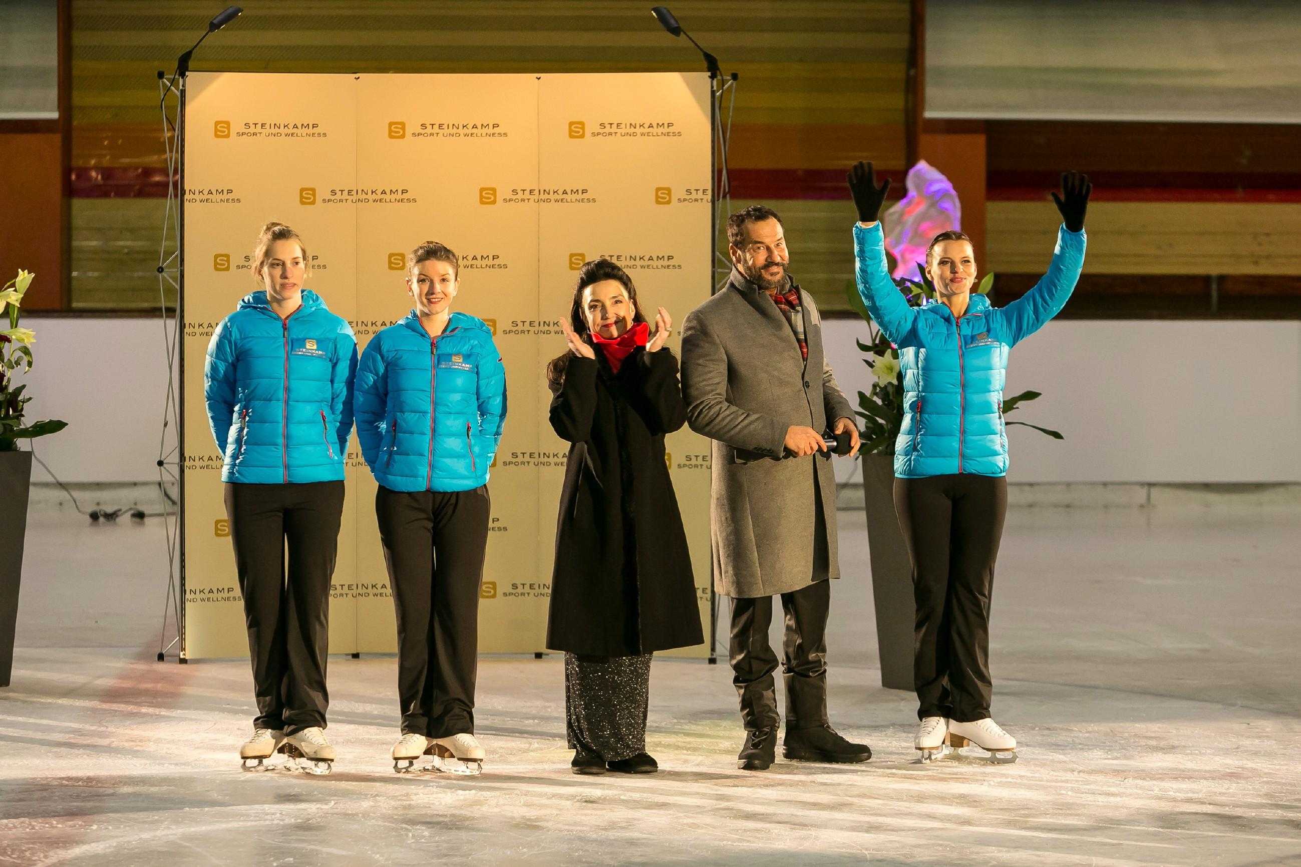 Gemeinsam mit Simone (Tatjana Clasing, M.) stellt Richard (Silvan-Pierre Leirich) den Gästen den neuen Eislaufkader (l. Komparsinnen) vor, dem nun auch Michelle (Franziska Benz, r.) angehört. (Quelle: RTL / Kai Schulz)