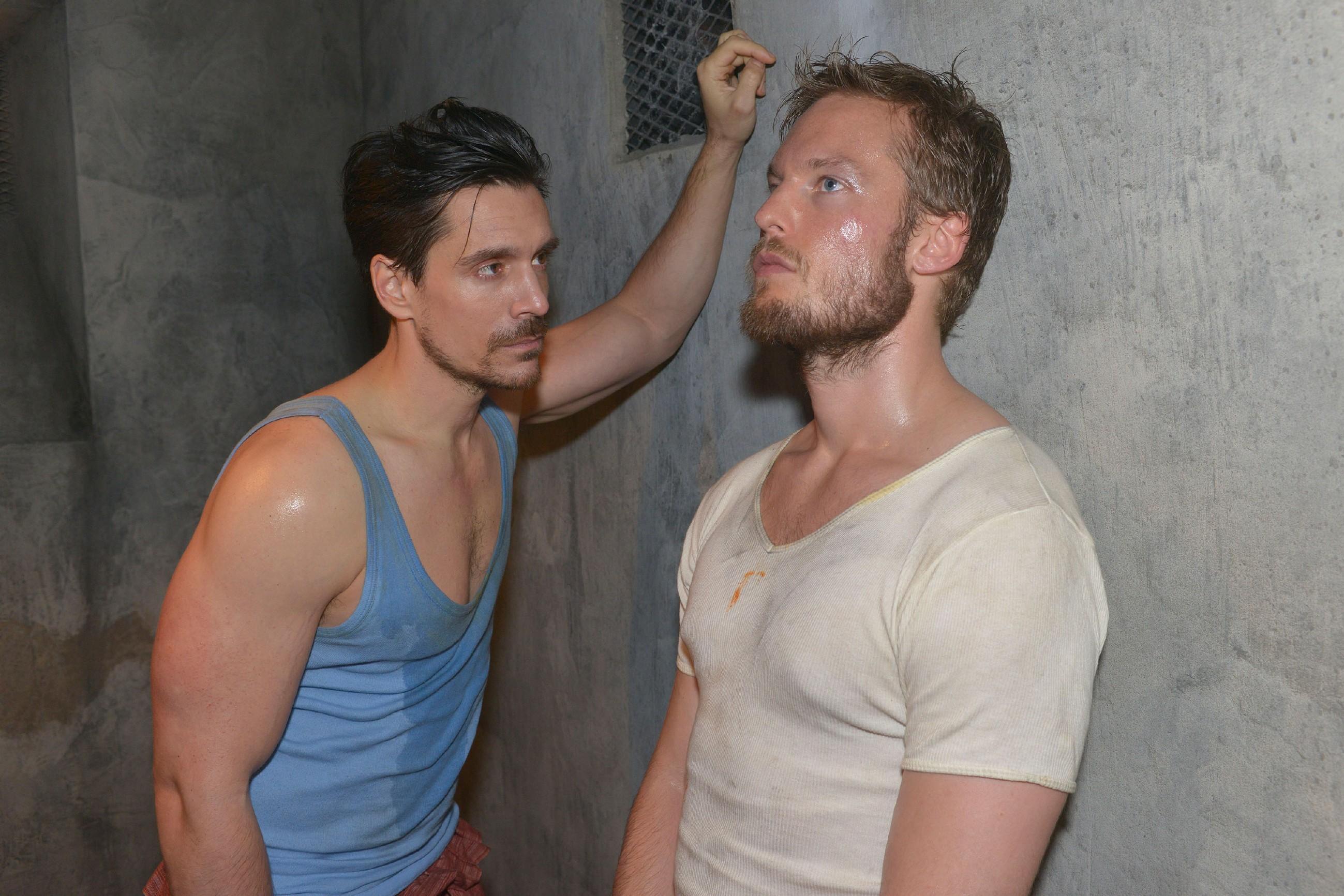 David (Philipp Christopher, l.) versucht im malaysischen Knast an das Handy seines Zellengenossen Tommy Zürner (Marc Bluhm) zu kommen, um Gerner um Hilfe zu bitten. (Quelle: RTL / Rolf Baumgartner)