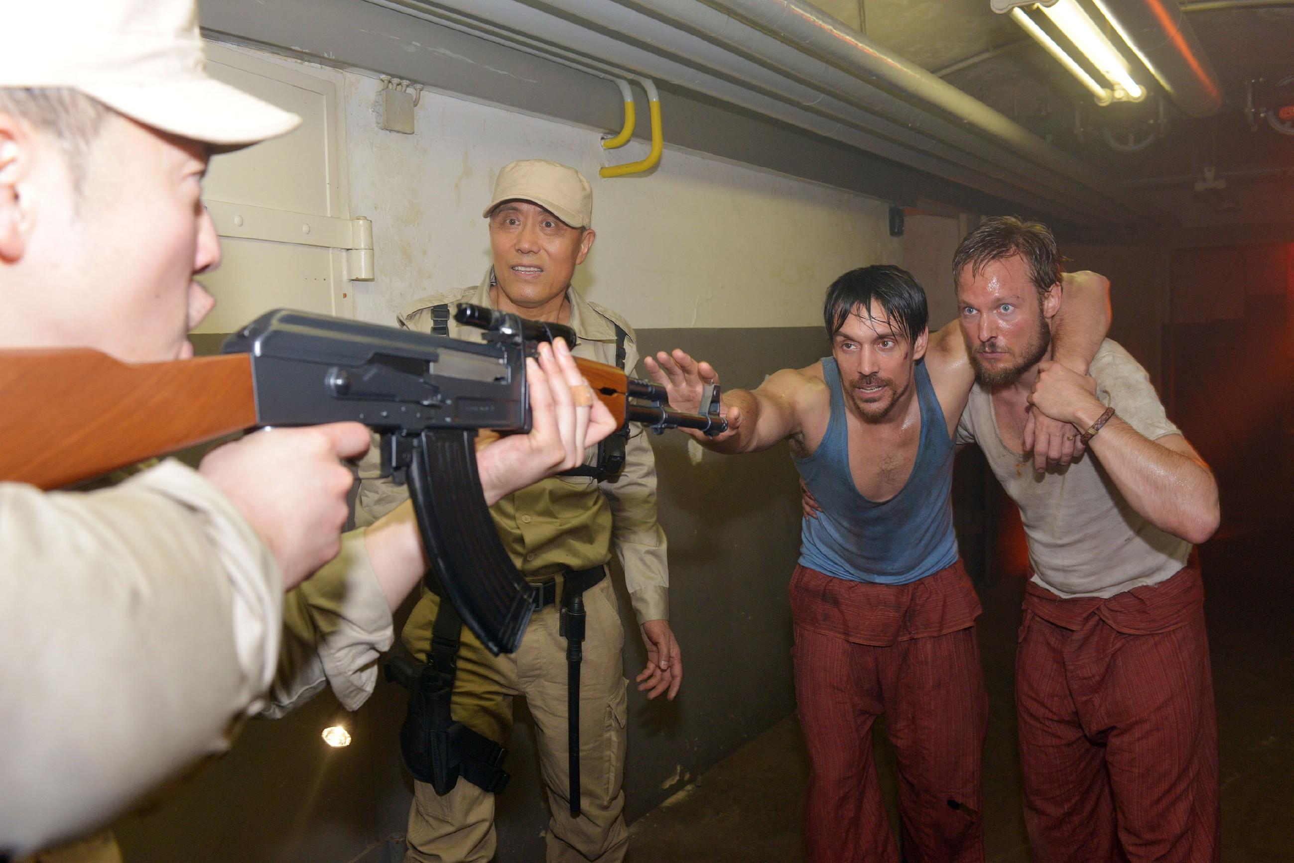 Davids (Philipp Christopher, 2.v.r.) und Tommys (Marc Bluhm, r.) Fluchtversuch aus dem malaysischen Gefängnis scheint an den bewaffneten Aufsehern (Komparsen) zu scheitern... (Quelle: RTL / Rolf Baumgartner)