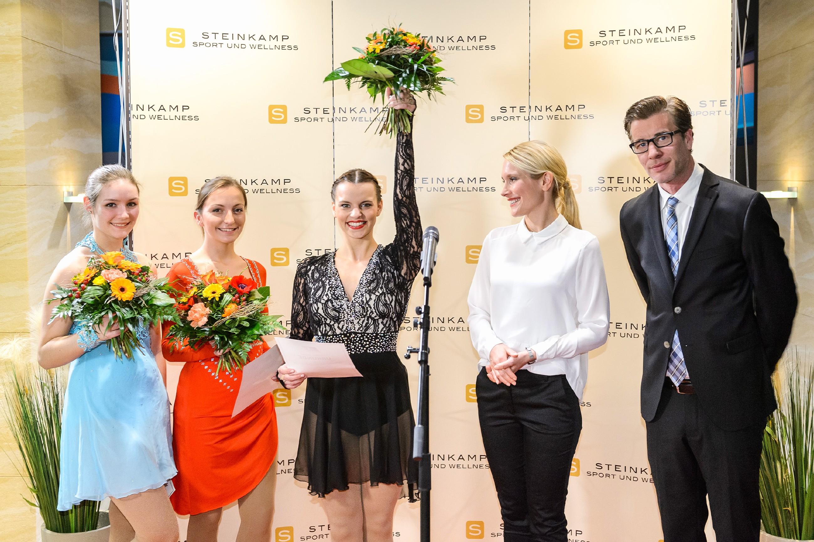 Stolz zeigt sich Michelle (Franziska Benz, M.) auf der Bühne der Presse, als sie neben zwei weiteren Eisläuferinnen (l. Komparsinnen) als Qualifikantin zur Deutschen Meisterschaft ausgerufen und von BDE-Präsidentin Theresa Hansen (Mareile Moeller, 2.v.r.) und Christoph (Lars Korten) beglückwünscht wird. (Quelle: RTL / Willi Weber)