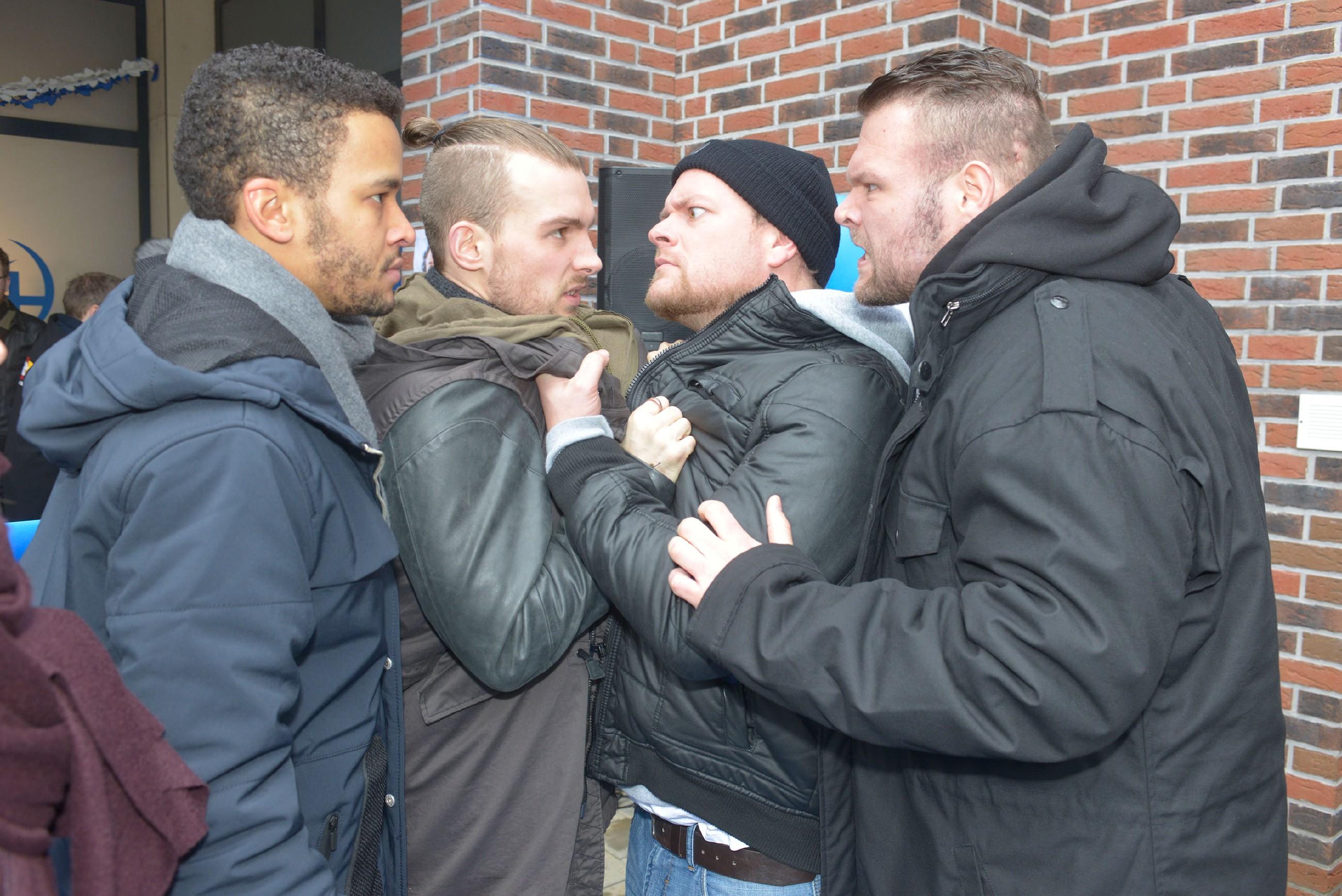 Chris (Eric Stehfest, 2.v.l.) stellt sich schützend vor Amar (Thando Walbaum, l.), der von aggressiven Rechtsradikalen (Komparsen) angepöbelt wird. (Quelle: RTL / Rolf Baumgartner)