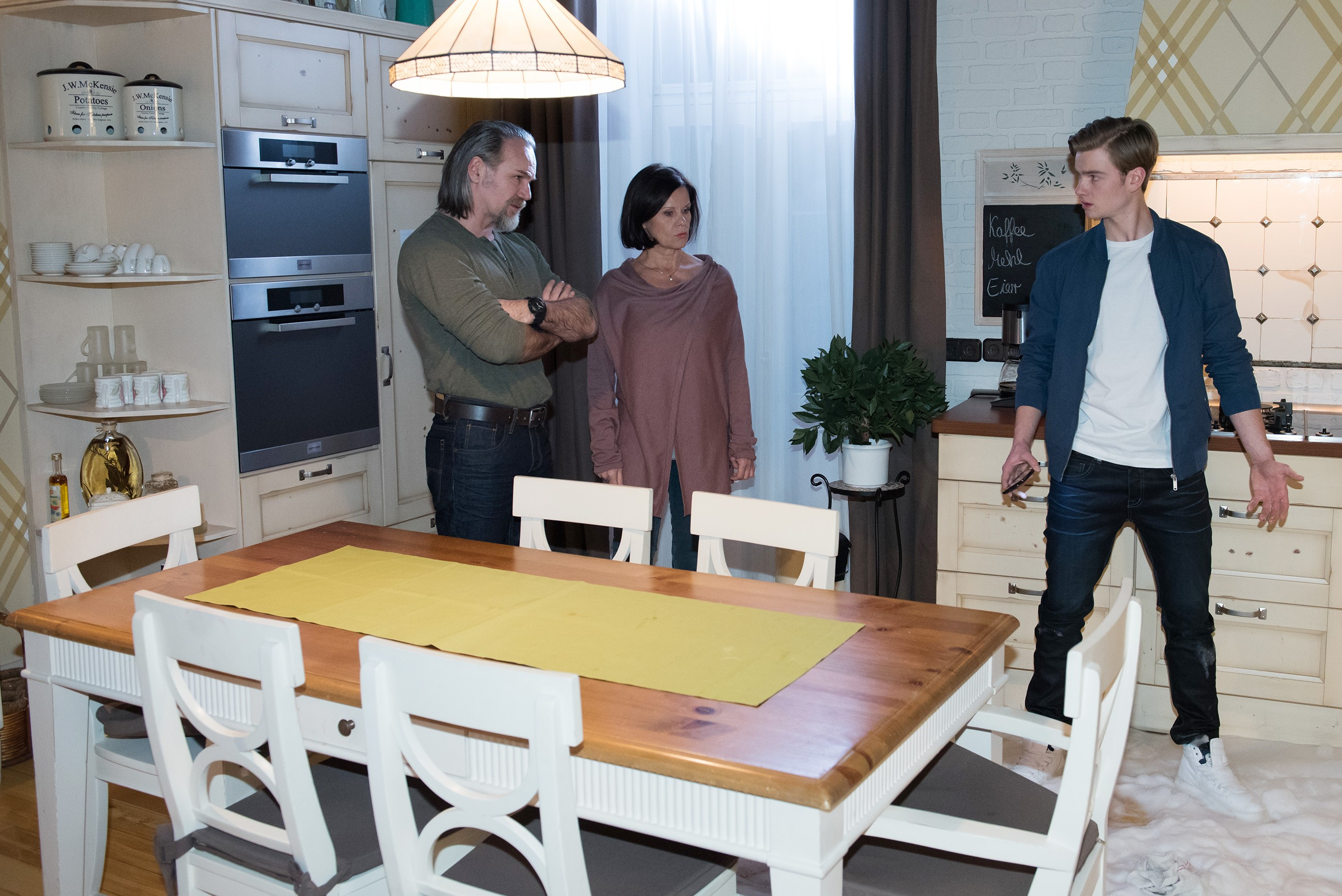 Valentin (Aaron Koszuta, r.) kann das selbstverschuldete Chaos in der Küche nicht vor Irene (Petra Blossey) und Robert (Luca Maric) verbergen.(Quelle: RTL / Stefan Behrens)