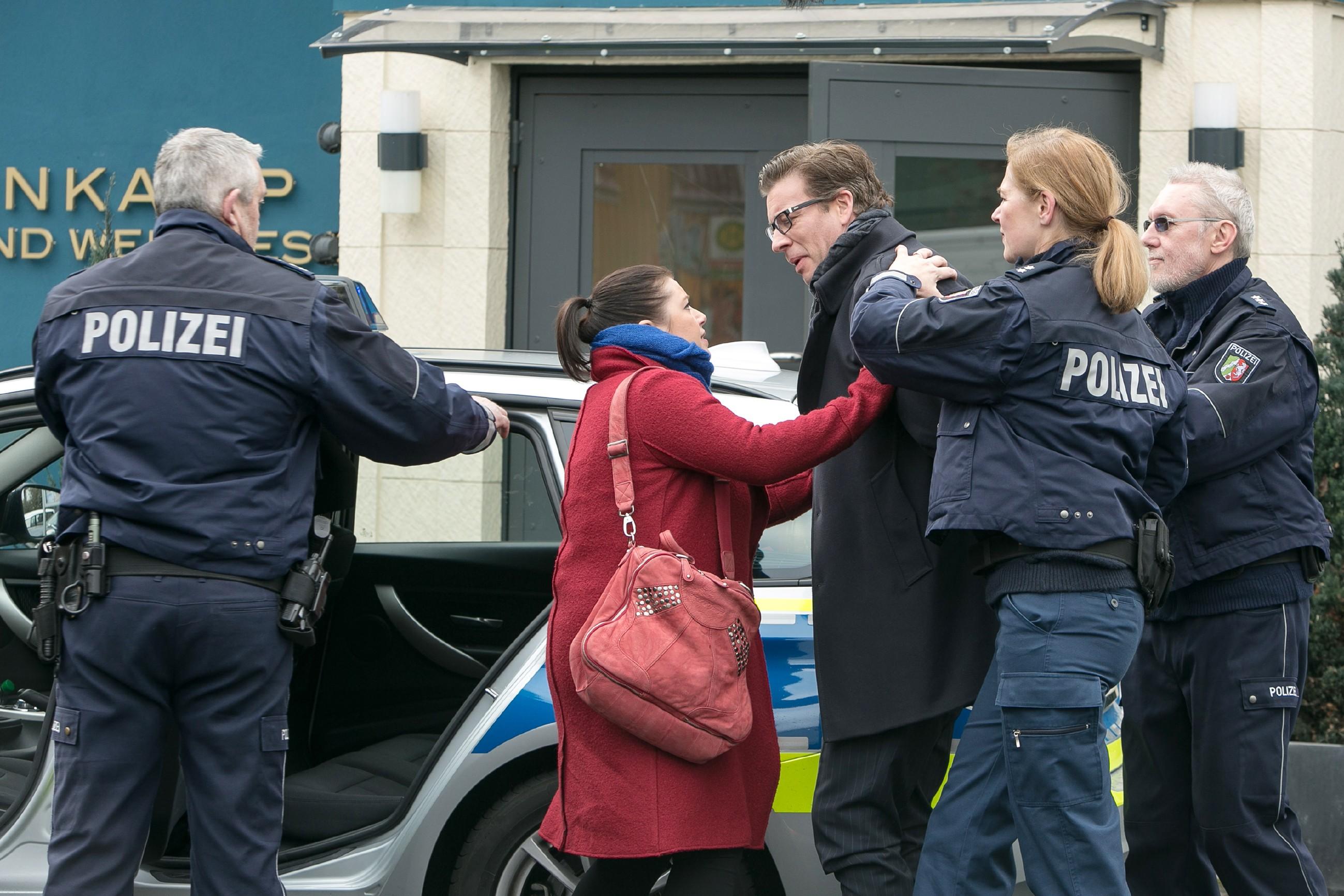 Vanessa (Julia Augustin, 2.v.l.) muss machtlos mitansehen, wie Christoph (Lars Korten, 3.v.r.) von den Polizisten (Komparsen) abgeführt wird. (Quelle: RTL / Kai Schulz)