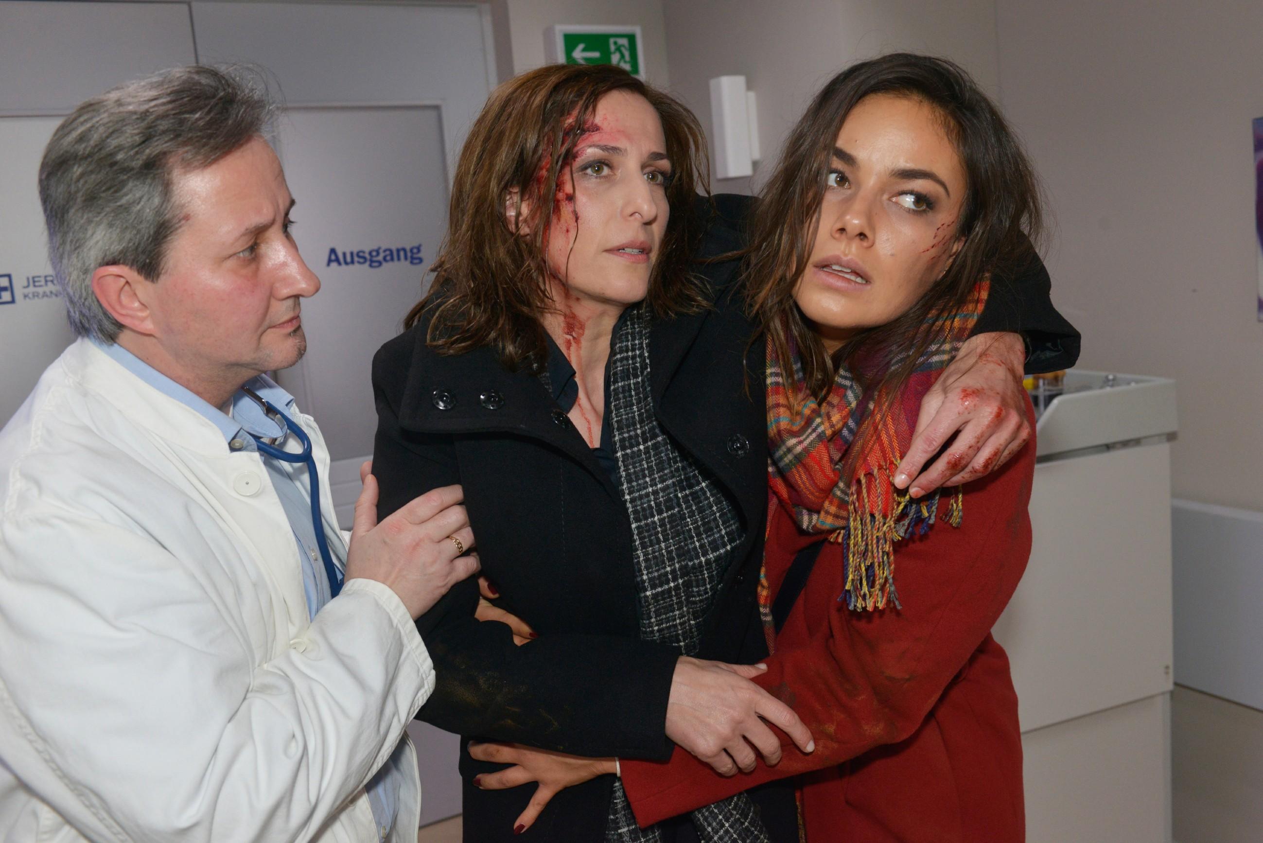 Jasmin (Janina Uhse, r.) bringt die verletzte Katrin (Ulrike Frank, M.) zu einem Arzt (Komparse) ins Krankenhaus und riskiert damit, festgenommen zu werden. (Quelle: RTL / Rolf Baumgartner)