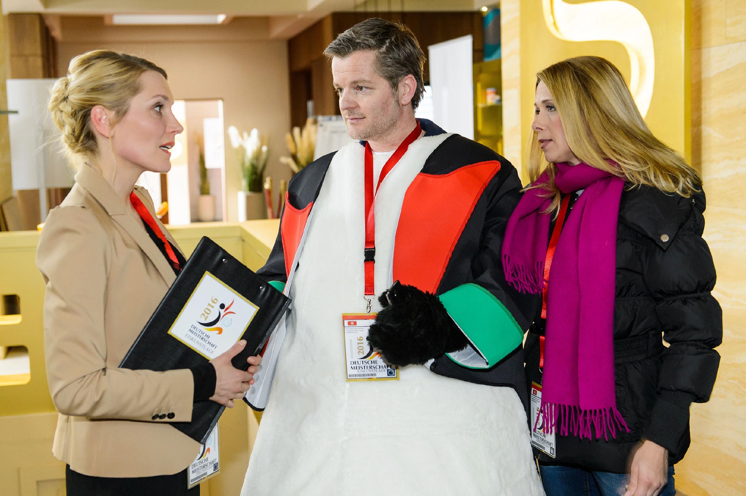 Diana (Tanja Szewczenko, r.) und Ingo (André Dietz) werden von Theresa Hansen (Mareile Moeller) darüber informiert, dass Marie vom Wettkampf disqualifiziert wird, wenn sie nicht rechtzeitig zur Kür auf dem Eis erscheint. (Quelle: RTL / Willi Weber)