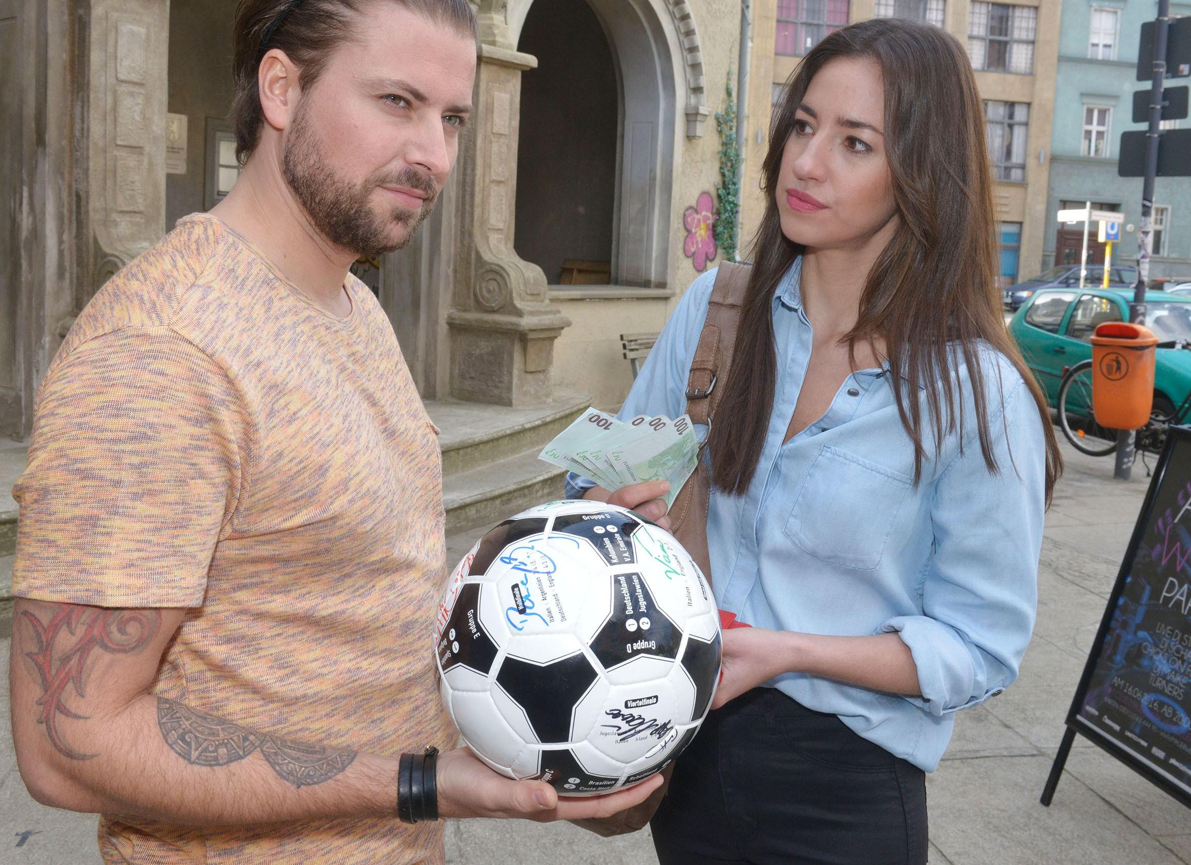 Elena (Elena Garcia Gerlach) hat im Internet einen überteuerten Ersatz-WM-Ball für Tuner ersteigert - ausgerechnet von John (Felix von Jascheroff), der sich ihr gegenüber bei der Übergabe unversöhnlich zeigt. (Quelle: RTL / Rolf Baumgartner)