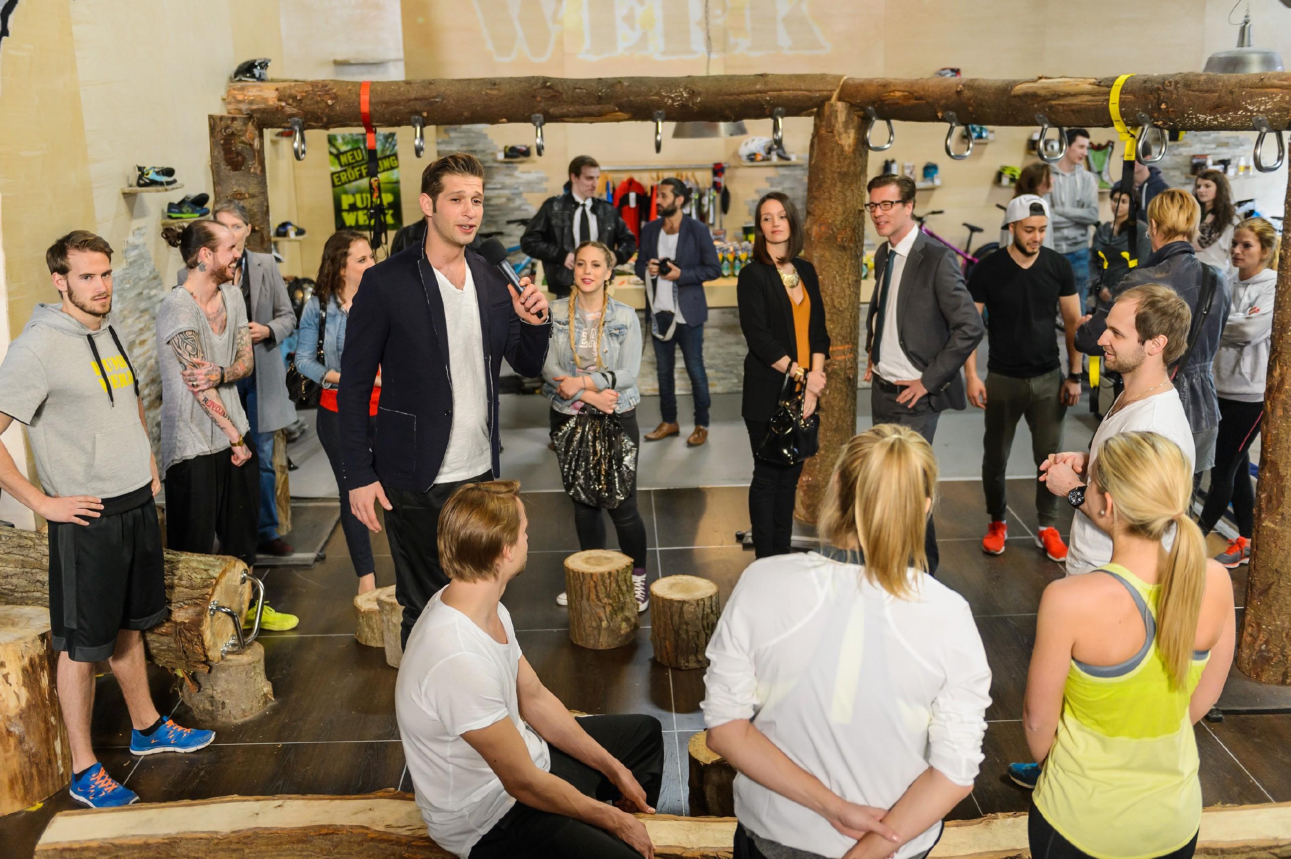 """Stolz eröffnet Deniz (Igor Dolgatschew, Mitte l.) das Pumpwerk und stellt dem Publikum die Einrichtung und das Konzept """"Fitness ohne Maschinen"""" vor. (Quelle: RTL / Willi Weber)"""