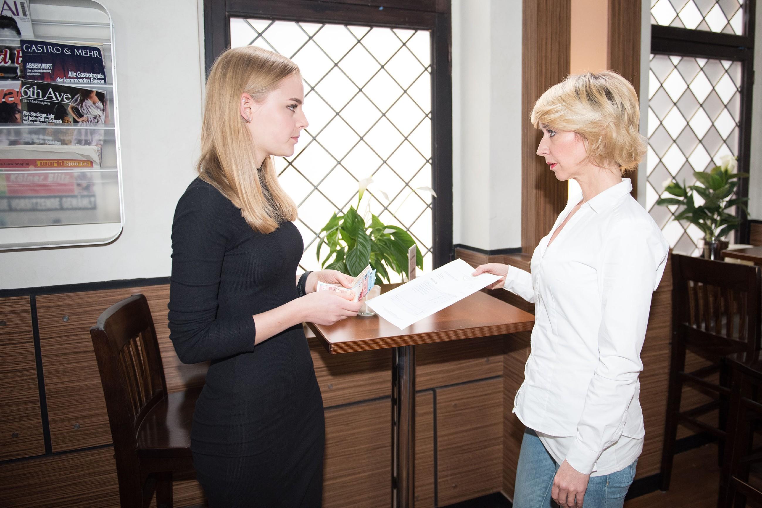 Als Ute (Isabell Hertel, r.) ihr die Rechnung präsentiert, muss Fiona (Olivia Burkhart) zu ihrem Schrecken feststellen, dass Rolfs Trauerfeier eine teure Angelegenheit war. (Quelle: RTL / Stefan Behrens)
