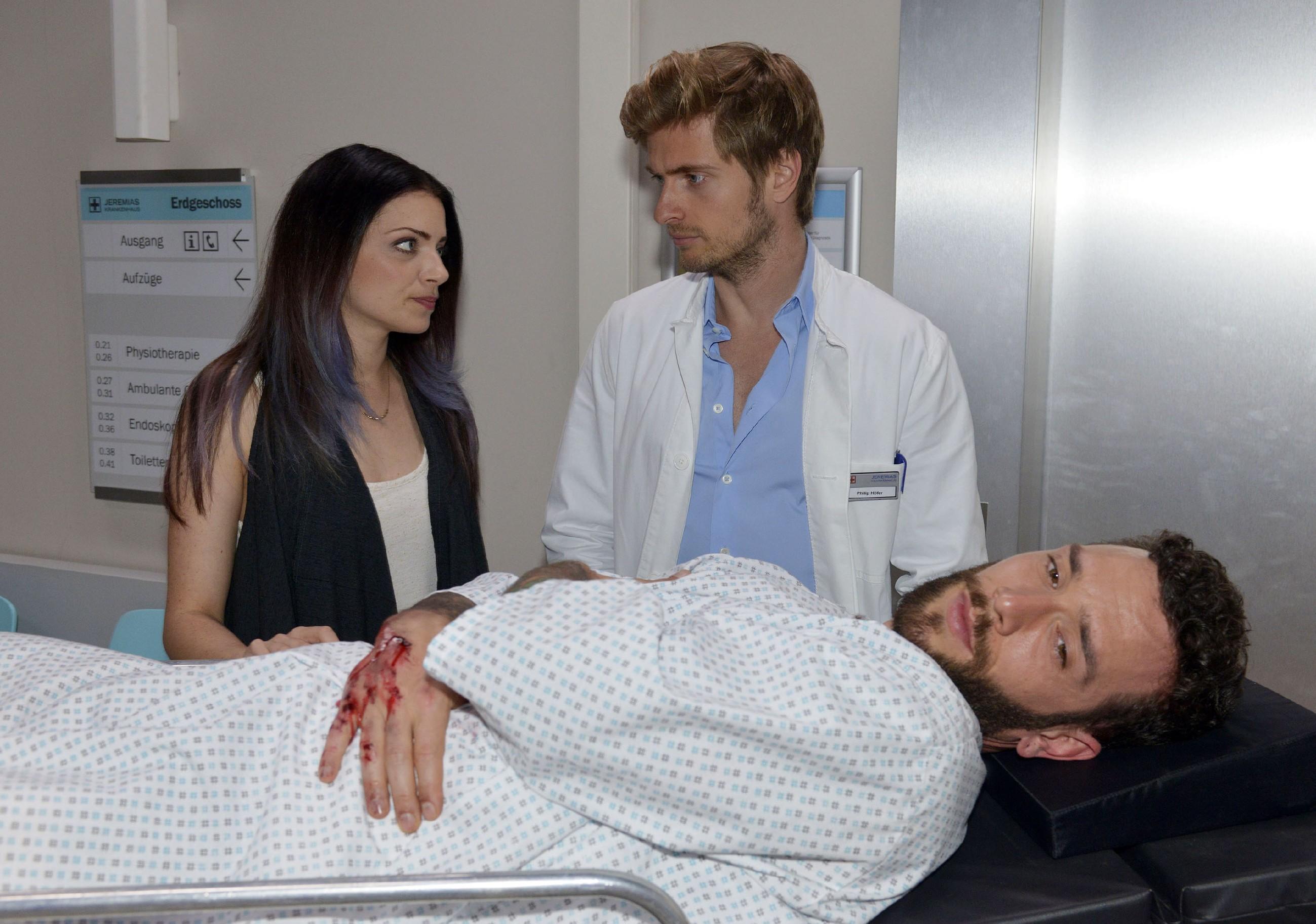 Emily (Anne Menden) ist Roberto (Sascha Pederiva, vorne) für dessen Rettungsaktion unendlich dankbar und begleitet ihn zu Philip (Jörn Schlönvoigt) ins Krankenhaus. (Quelle: RTL / Rolf Baumgartner)