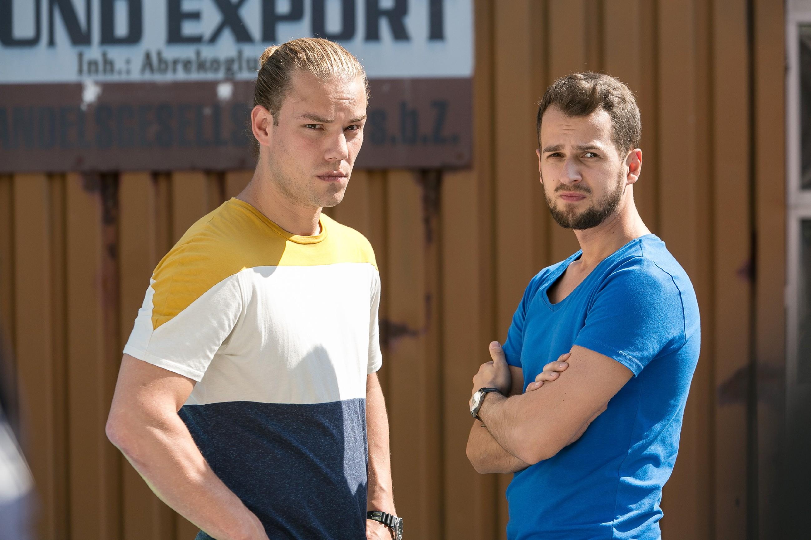 Leo (Julian Bayer, l.) und Tobi (Michael Jassin) schauen zu, wie Marian, nachdem er absichtlich vor Leos Auto gesprungen ist, mit dem Krankenwagen abtransportiert wird. (Quelle: RTL / Kai Schulz)