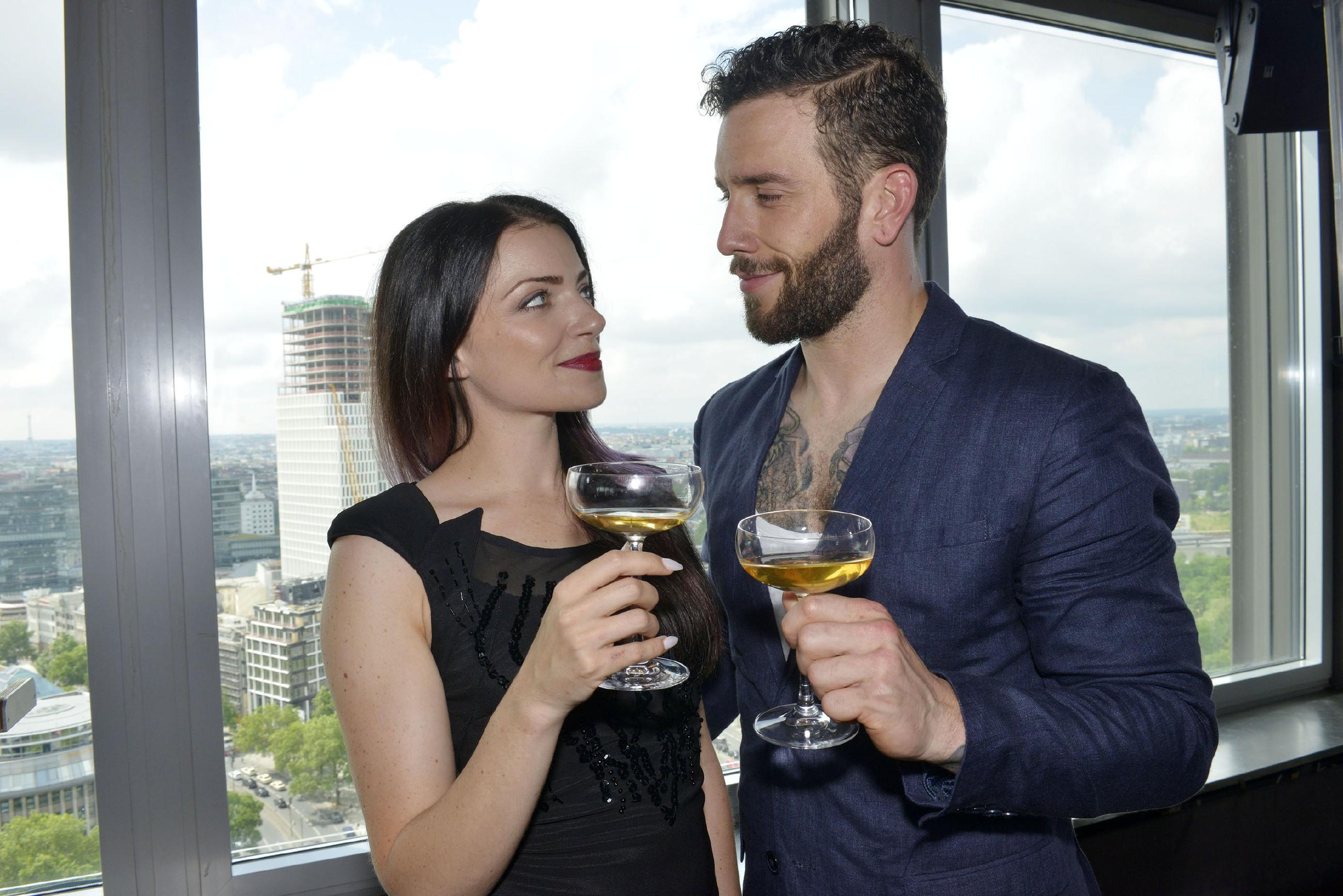 """Emily (Anne Menden) stößt mit Roberto (Sascha Pederiva), der als ihr Begleiter zu dem """"Glanz & Glamour""""-Event eingesprungen ist, auf den Erfolg von Tussi Attack an. (Quelle: RTL / Rolf Baumgartner)"""