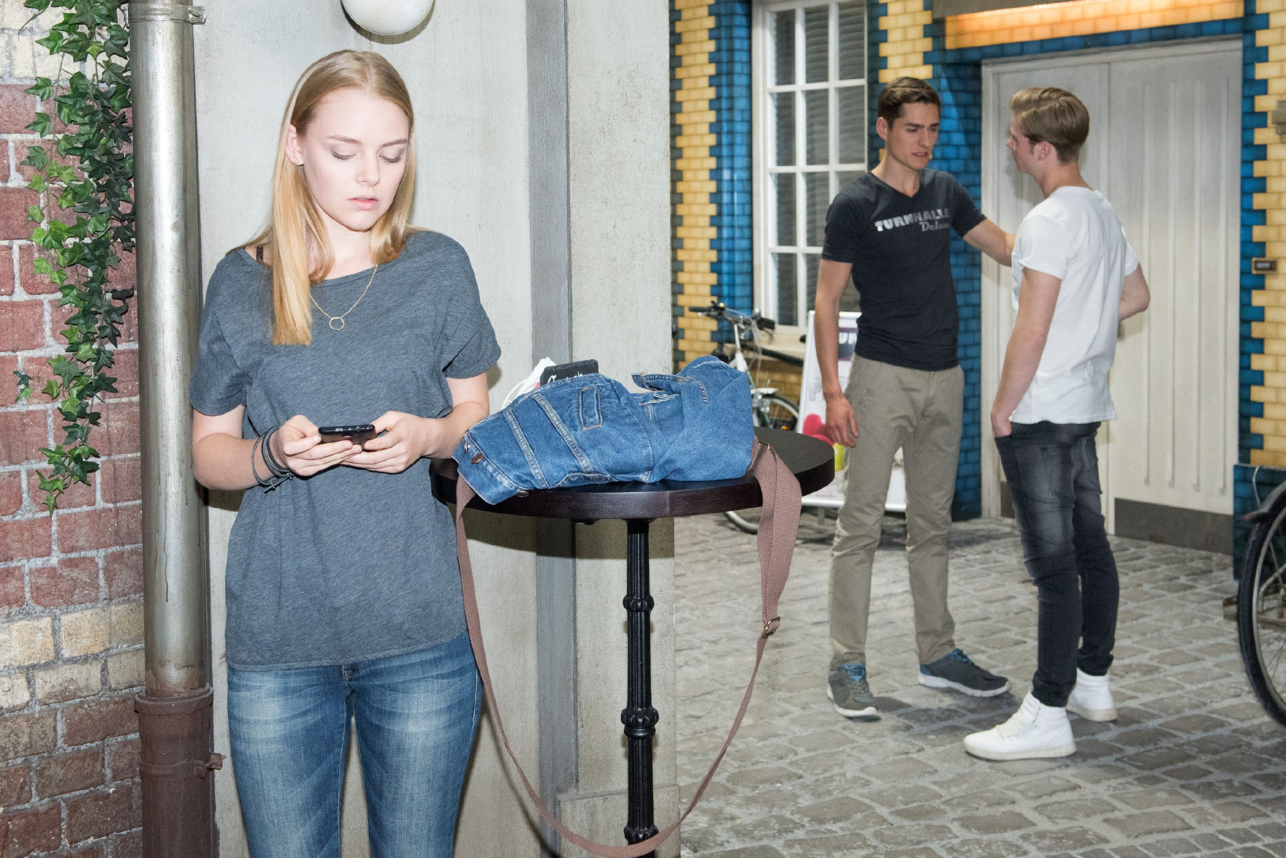Fiona (Olivia Burkhart) klaut mit Ringos (Timothy Boldt) Hilfe Valentins (Aaron Koszuta, r.) Handy, um dessen Vater Benedikt in eine Falle zu locken. (Quelle: RTL / Stefan Behrens)