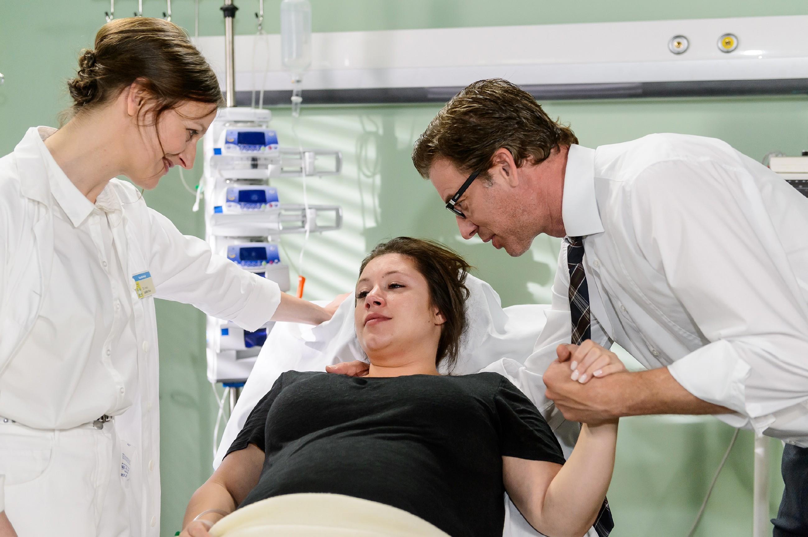 Vanessa (Julia Augustin, M.) und Christoph (Lars Korten) atmen auf, als Dr. Fink (Barbara Seifert) Entwarnung gibt: Offenbar wurde die Blutung durch eine bislang unentdeckte Zyste ausgelöst, die sich geöffnet hat. (Quelle: RTL / Willi Weber)