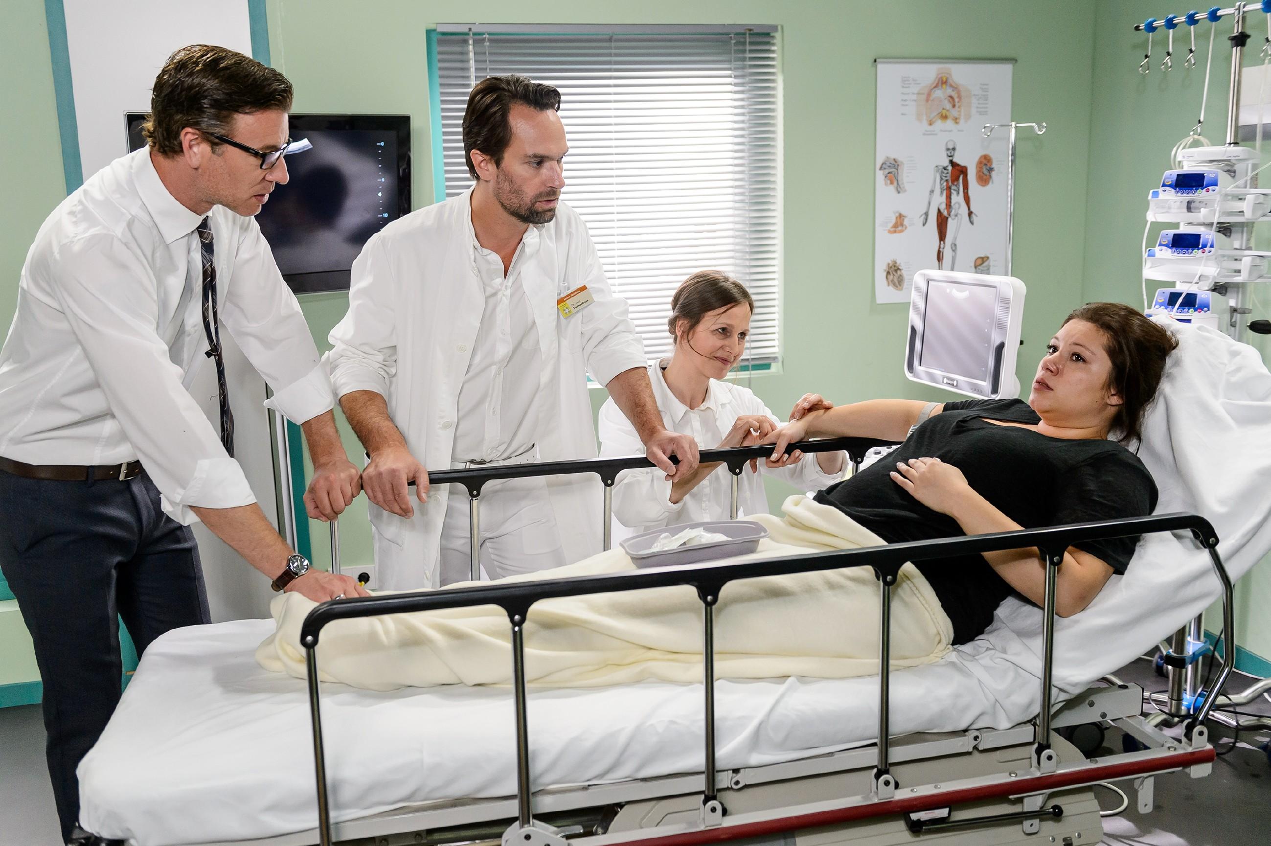 Christoph (Lars Korten, l.) und Thomas (Daniel Brockhaus) begleiten Vanessa (Julia Augustin, r.) in den Behandlungsraum, wo sie von Dr. Fink (Barbara Seifert) wegen den Blutungen untersucht werden soll. (Quelle: RTL / Willi Weber)