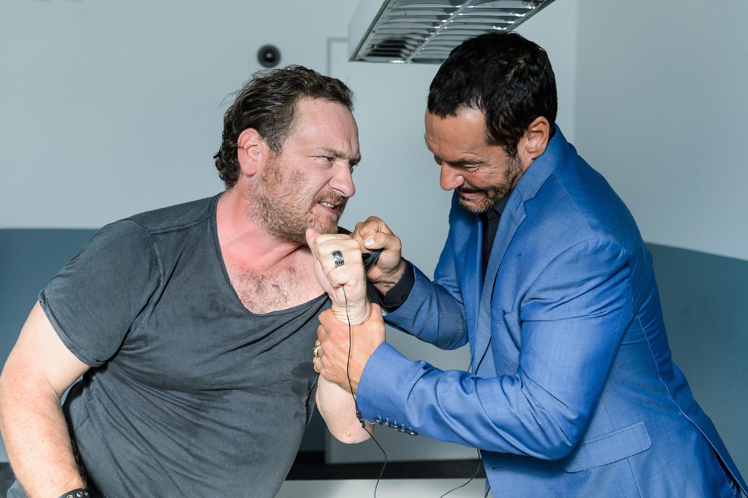 Der von der Polizei verkabelte Richard (Silvan-Pierre Leirich, r.) lässt sich von Kerber (Marcus Jakovljevic) bei einem vorgetäuschten Streit das Mikrofon entreißen, um mit ihm die Details des Waffendeals zu besprechen. (Quelle: RTL / Willi Weber)