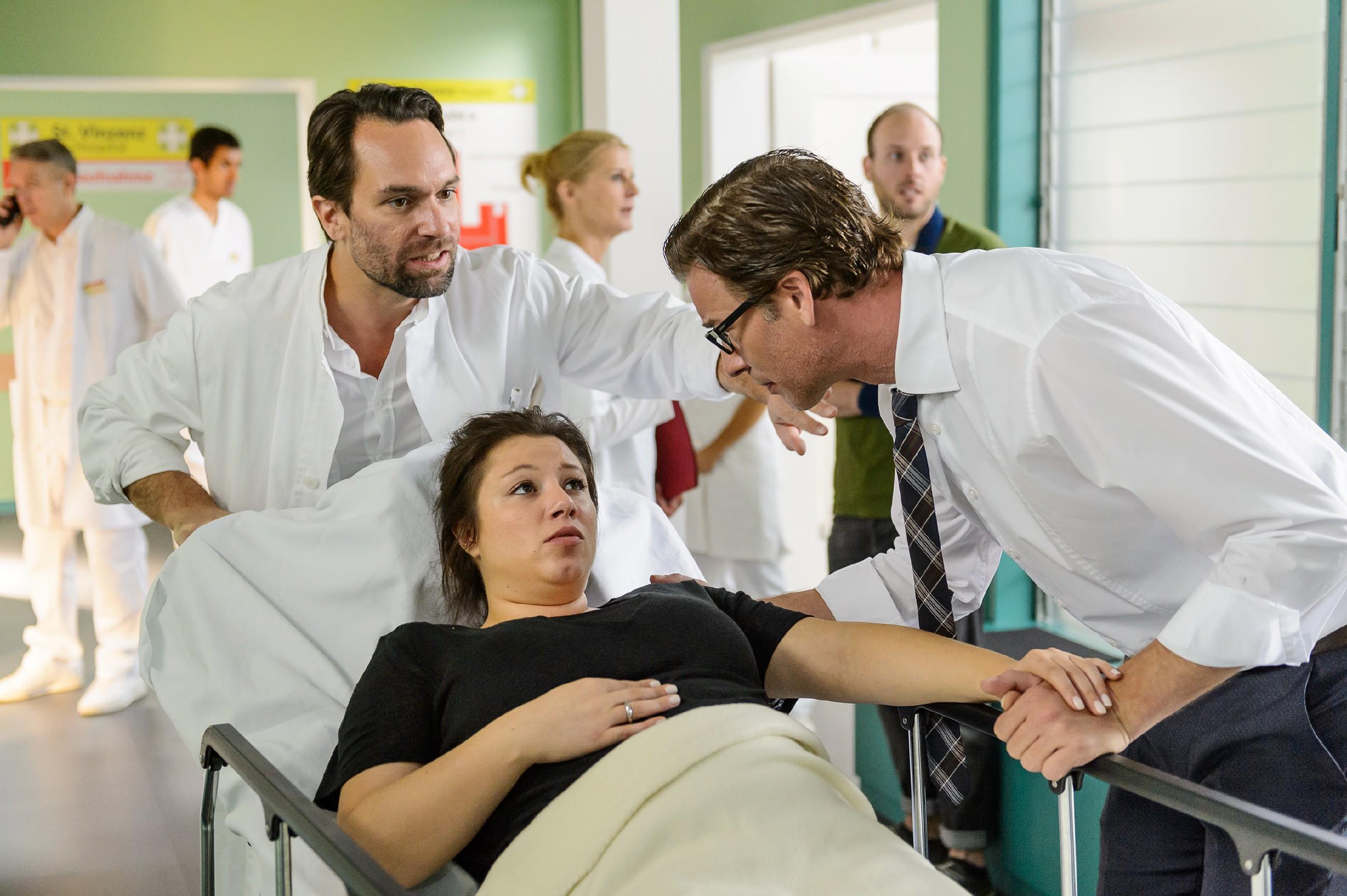 Vanessa (Julia Augustin) hatte in der Nacht Blutungen, weshalb Christoph (Lars Korten, r.) sie ins Krankenhaus gefahren hat. Thomas (Daniel Brockhaus) bringt die beiden in ein Behandlungszimmer zu Vanessas Ärztin Dr. Fink.