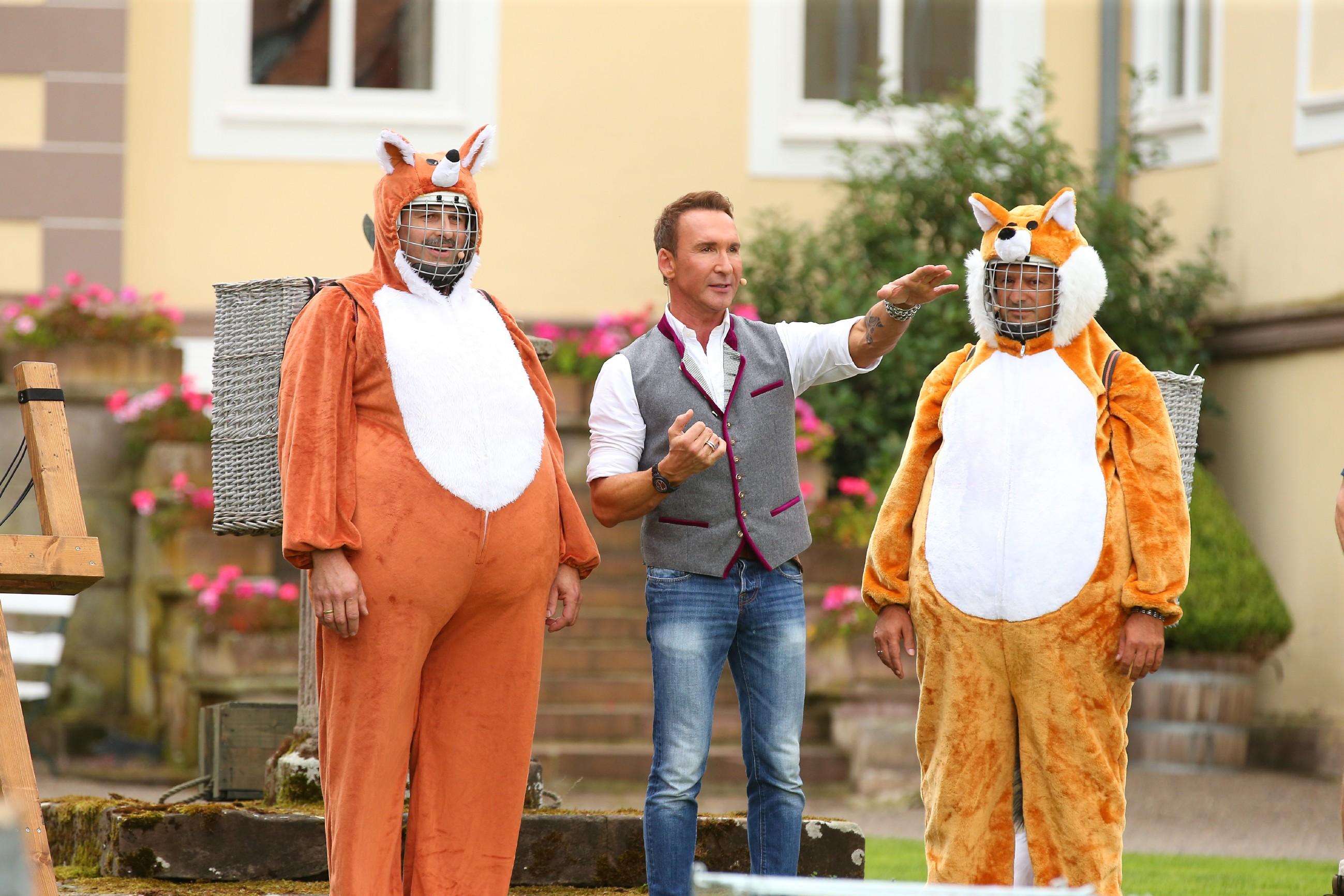 """Beim Spiel """"Alarm im Hühnerstall"""" sind Bauer Josef (l.) und Detlef Steves als fiese Füchse unterwegs. In der Mitte Jochen Bendel - Co-Moderator, Kommentator und Schiedsrichter."""