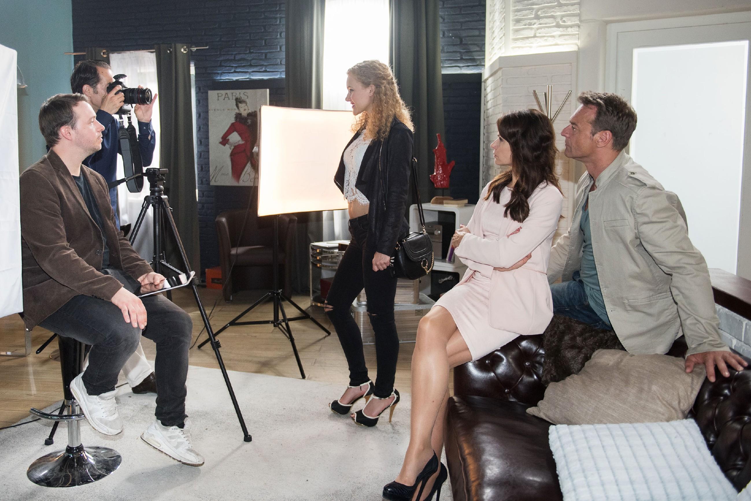 Während der Homestory-Reportage bei Rufus (Kai Noll, r.) und Britta (Tabea Heynig, 2.v.r.) drängt sich KayC (Pauline Angert, M.) zu Brittas Unmut gekonnt in den Vordergrund (l. Komparsen) (Quelle: RTL / Stefan Behrens)