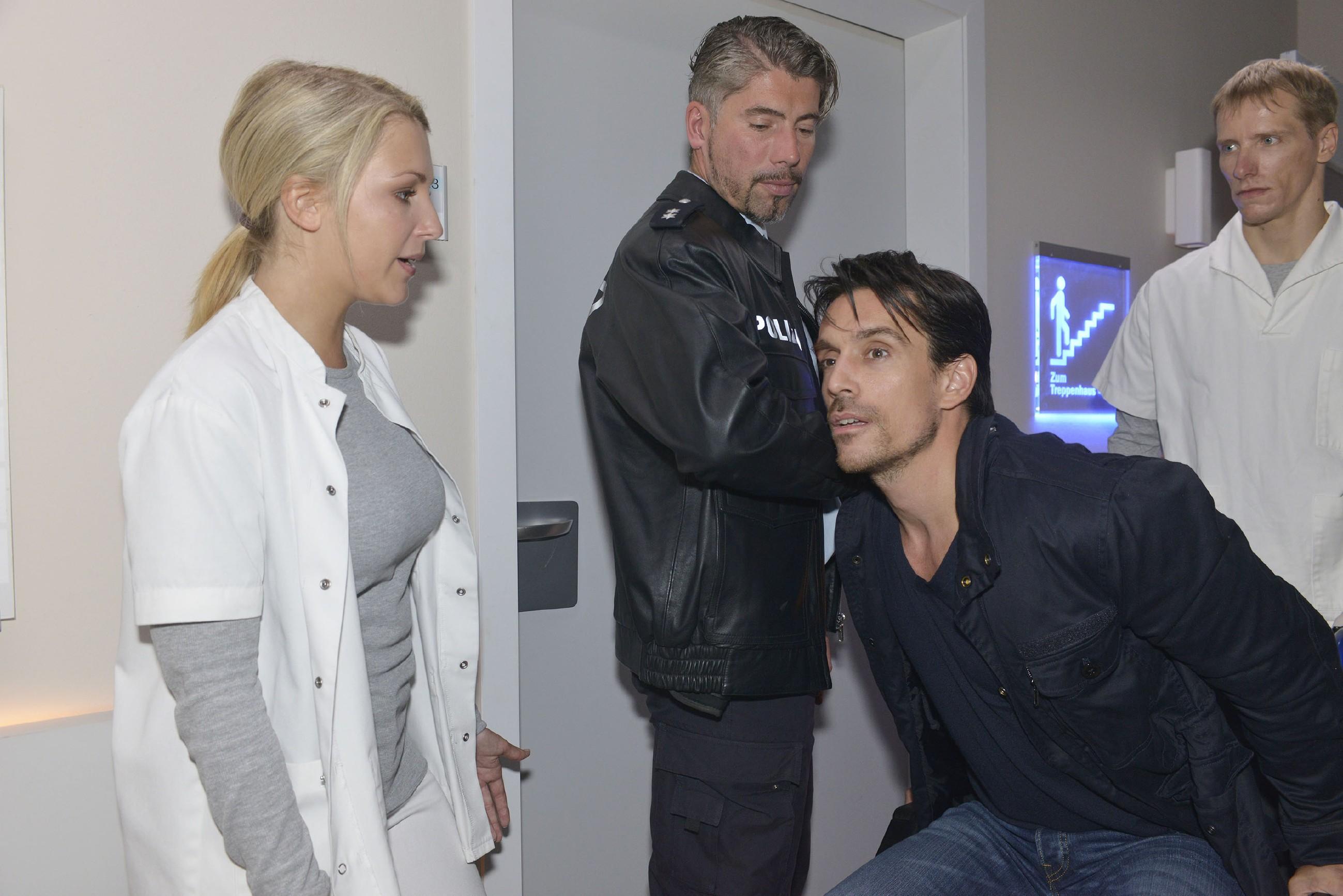 Als David (Philipp Christopher, 2.v.r.) in Begleitung eines Polizisten (Komparse) von einem Sanitäter (Komparse) ins Krankenhaus gebracht wird und zu der verletzten Ayla will, versucht Lilly (Iris Mareike Steen) ihn zu beruhigen.