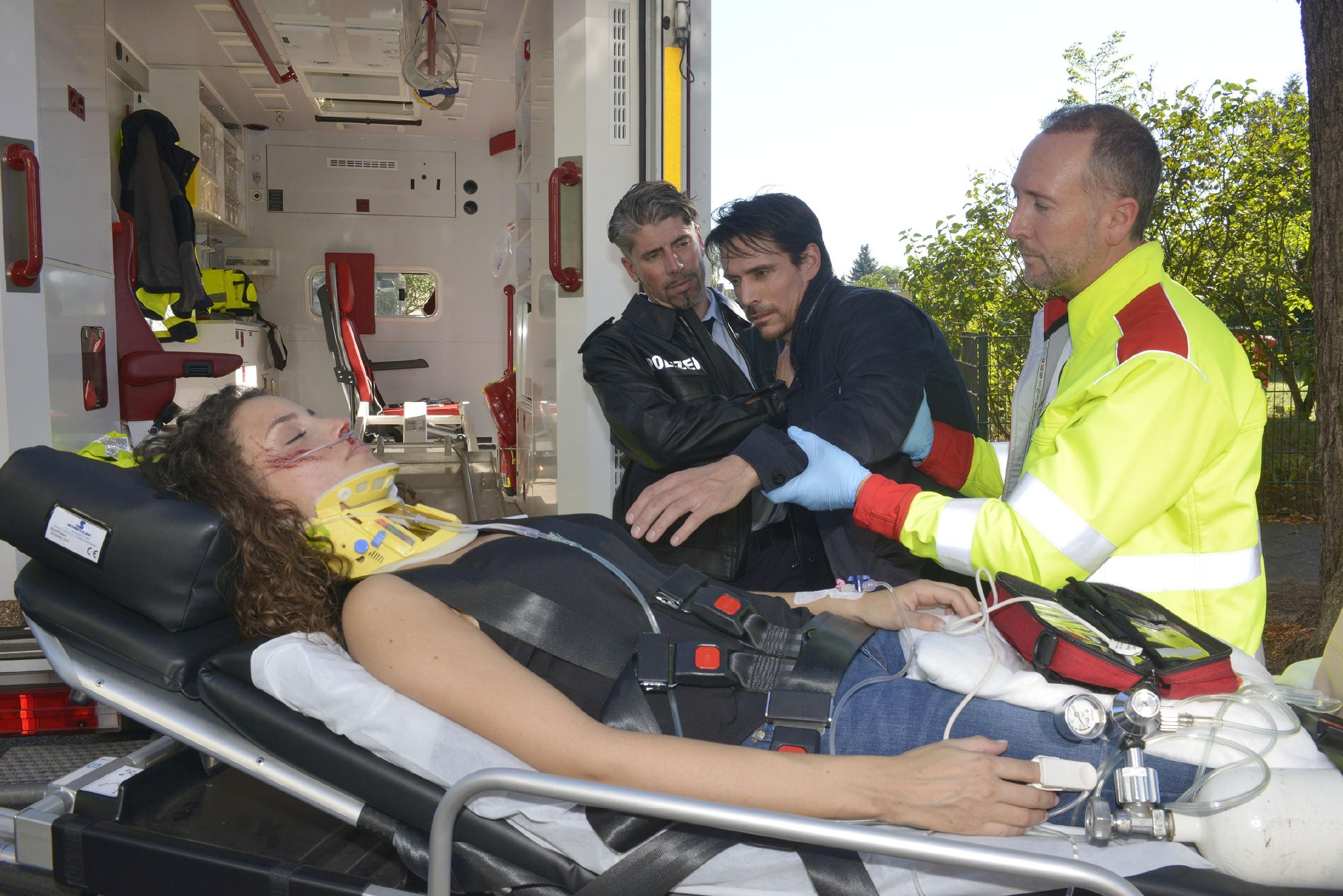 Ein Polizist (Komparse) und ein Sanitäter (Komparse) versuchen David (Philipp Christopher, 2.v.r.) zu beruhigen, der vor Sorge um die verletzte Ayla (Nadine Menz) völlig neben sich steht und nicht ahnt, dass er selbst verdächtigt wird, Ayla angefahren zu haben. (Quelle: RTL / Rolf Baumgartner)