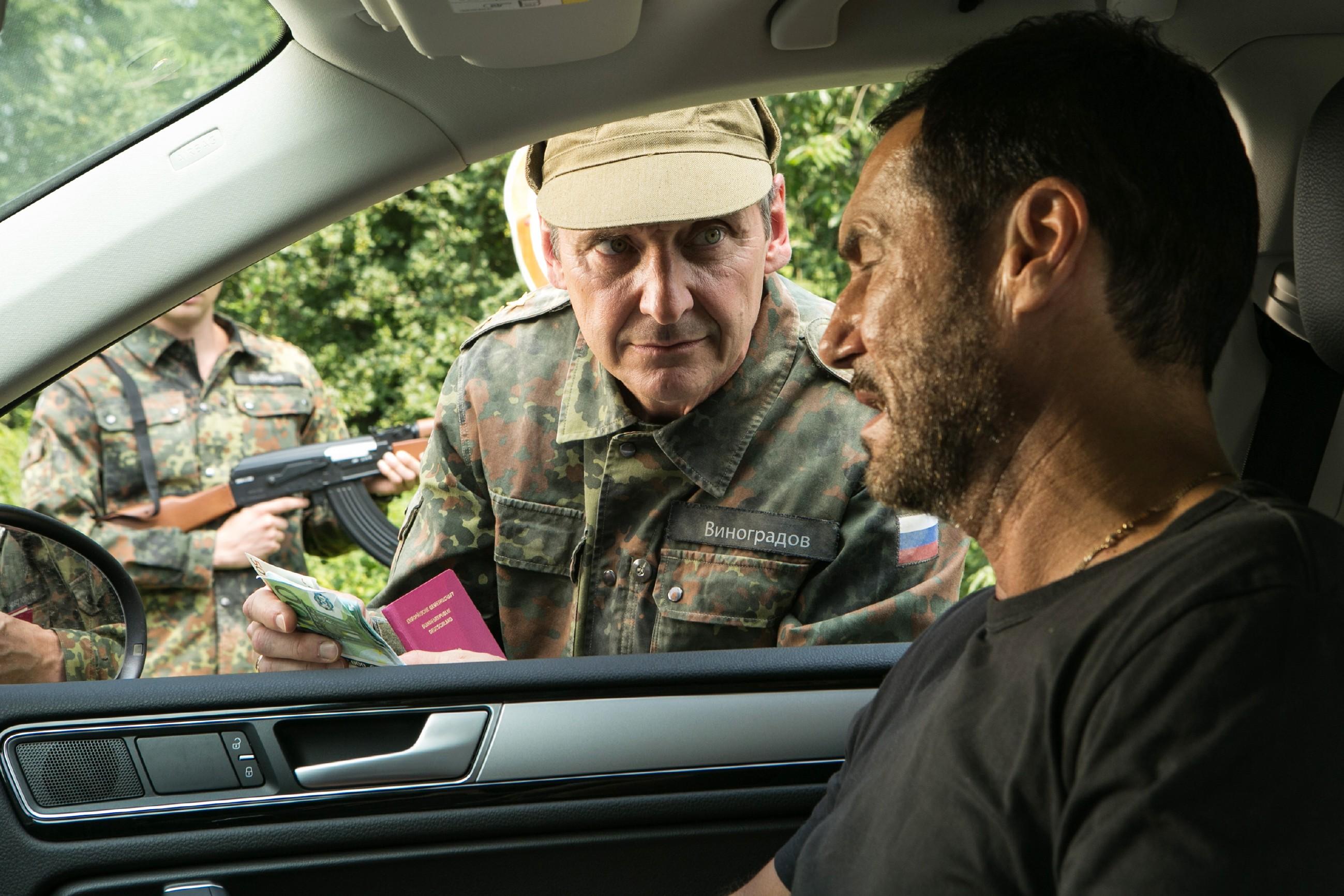 Richard (Silvan-Pierre Leirich, r.) gerät mit Ben in eine Grenzkontrolle und versucht den russischen Beamten Andrej (Andrej Kaminsky) zu bestechen, damit dieser nicht den Kofferaum mit den Waffen kontrolliert.