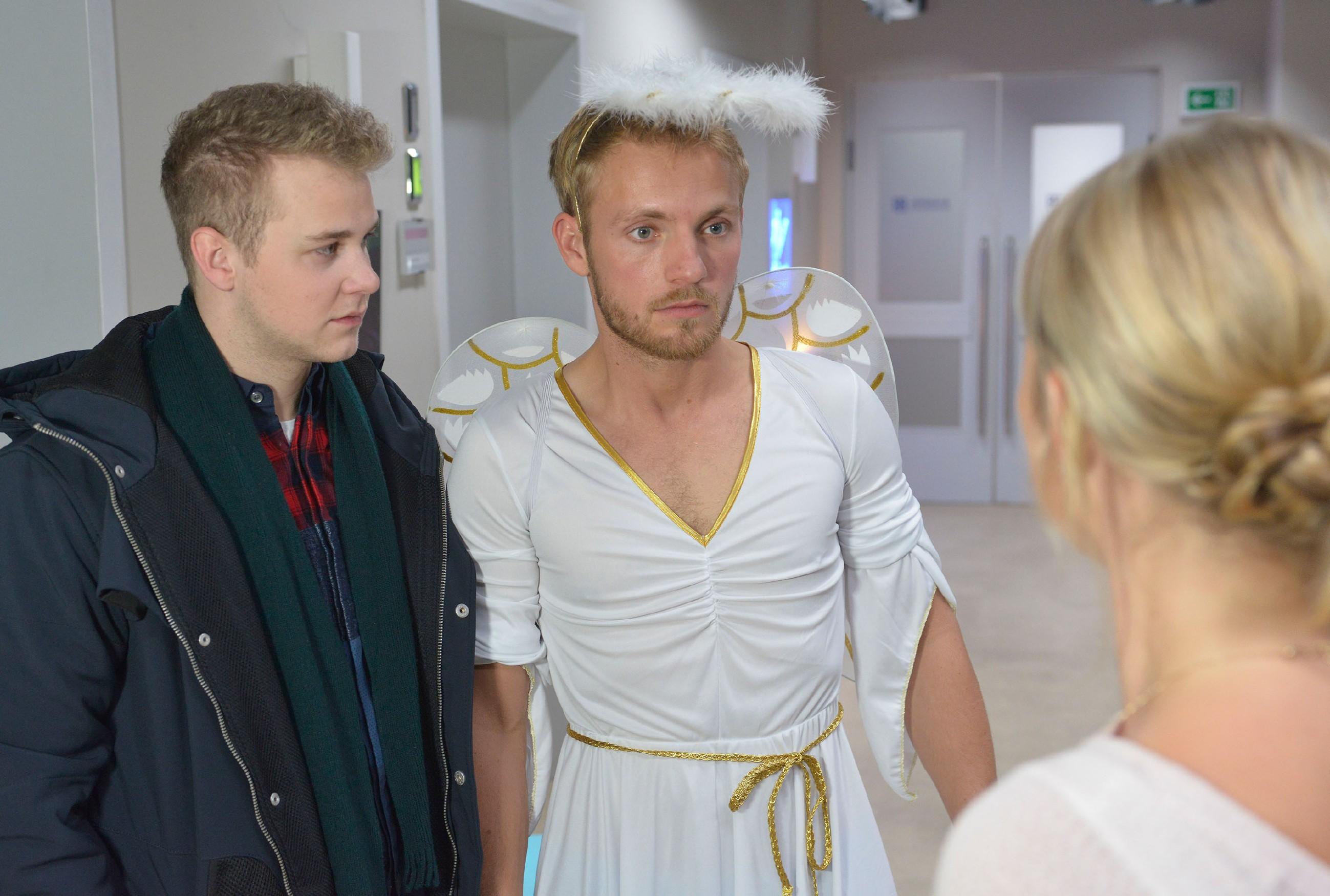 Jonas (Felix van Deventer, l.) sieht schuldbewusst mit an, wie Paul (Niklas Osterloh) im peinlichen Engelskostüm vor seiner Ex steht. (Quelle: RTL / Rolf Baumgartner)