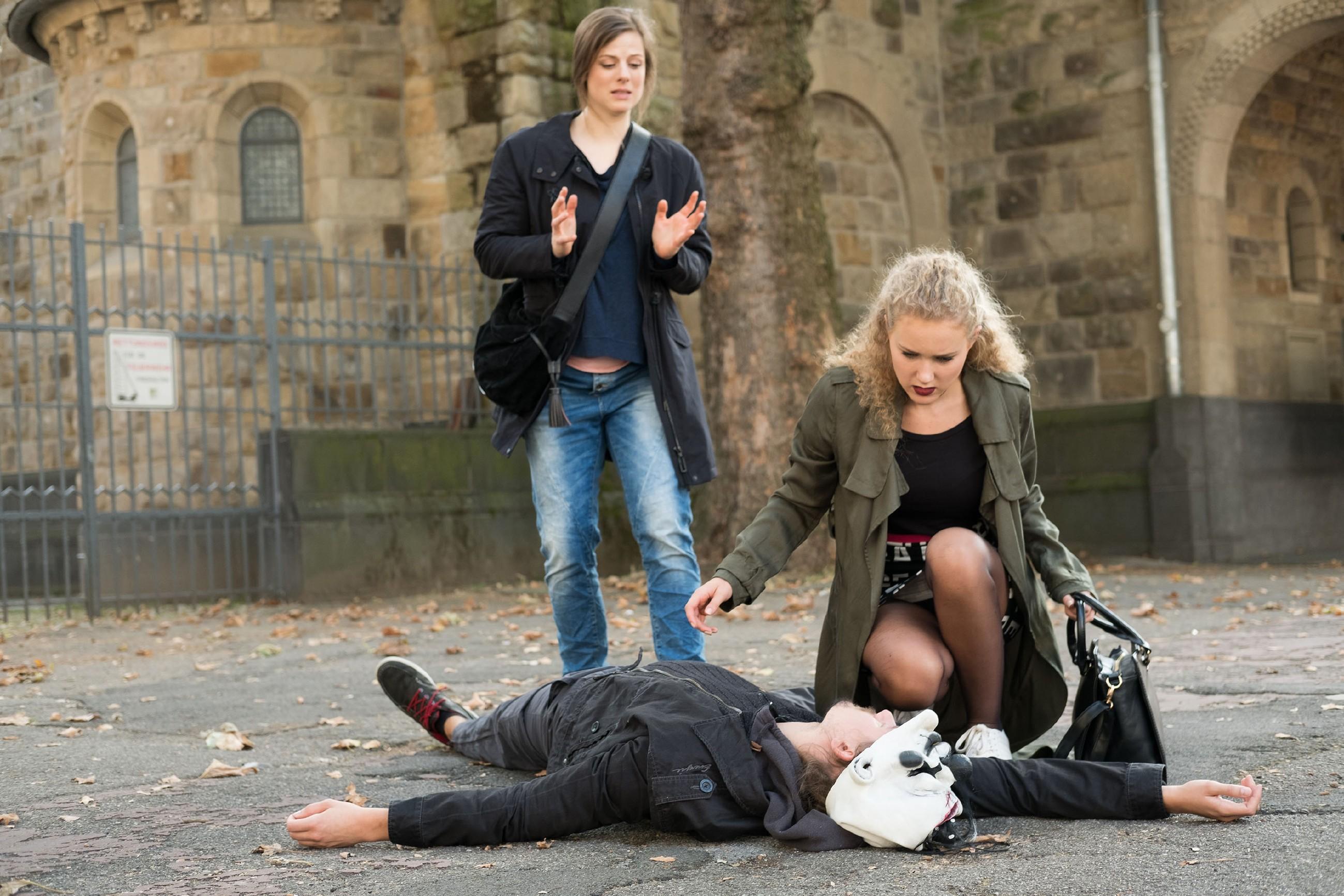 KayC (Pauline Angert, r.) glaubt, dass der Clown von Elli (Nora Koppen, l.) engagiert wurde, schlägt den Mann (Komparse) nieder und zieht ihm die Maske ab - doch statt in ein bekanntes Gesicht blickt sie in das eines echten Räubers... (Quelle: RTL / Stefan Behrens)