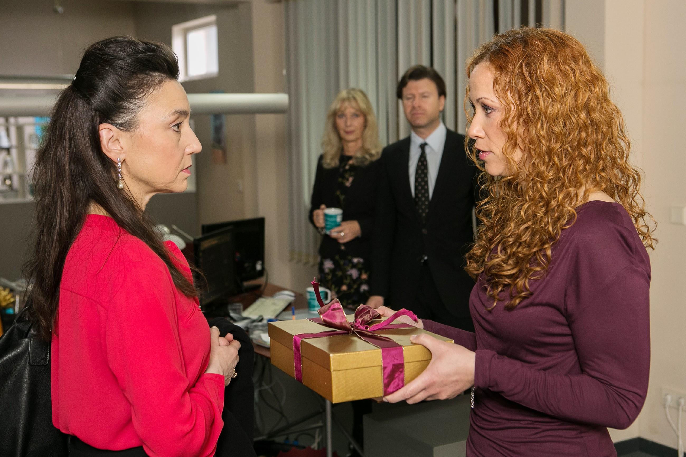 Simone (Tatjana Clasing, l.) bekommt von Brigitte (Madlen Kaniuth) ein Weihnachtsgeschenk überreicht und versucht - trotz ihrer großen Sorge um Richard - vor ihren Mitarbeitern die Haltung bewahren. (Quelle: RTL / Kai Schulz)