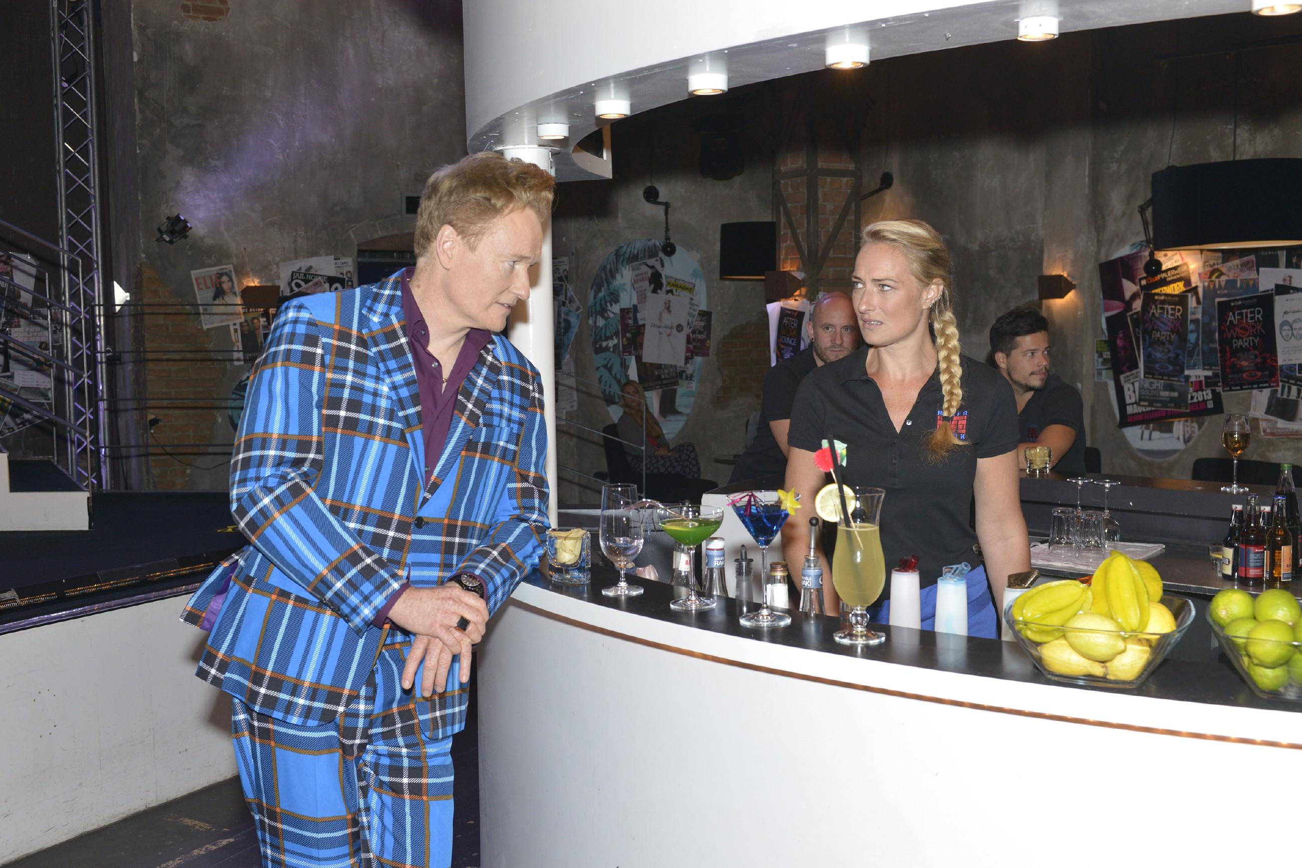 Maren (Eva Mona Rodekirchen) hat gerade ihre Schicht hinter dem Tresen angetreten hat, wird von Johnny J. Smith (US-Talkmaster Conan O'Brien), einem extravagant gekleideten Modedesigner, angesprochen.