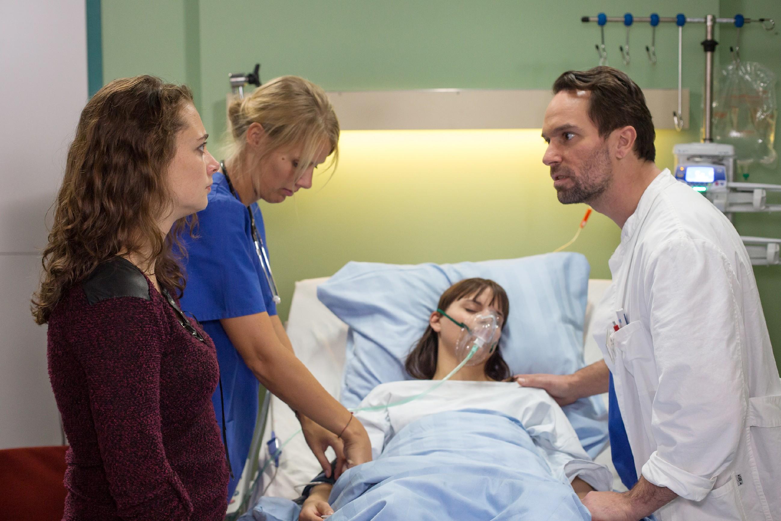 Während sich eine Krankenschwester (2.v.l. Komparsin) und Thomas (Daniel Brockhaus) um Michelle (Franziska Benz, lieg.) kümmern, fürchtet Carmen (Heike Warmuth) um das Leben ihrer Tochter ... (Quelle: RTL / Michael Böhme)