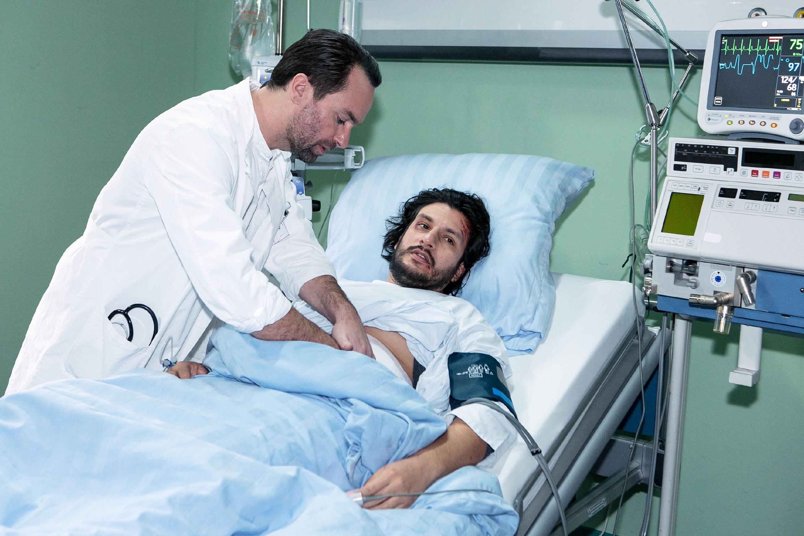 Maximilian (Francisco Medina, r.) wird von Thomas (Daniel Brockhaus) untersucht und erkennt seine aussichtslose Lage. (Quelle: RTL / Kai Schulz)