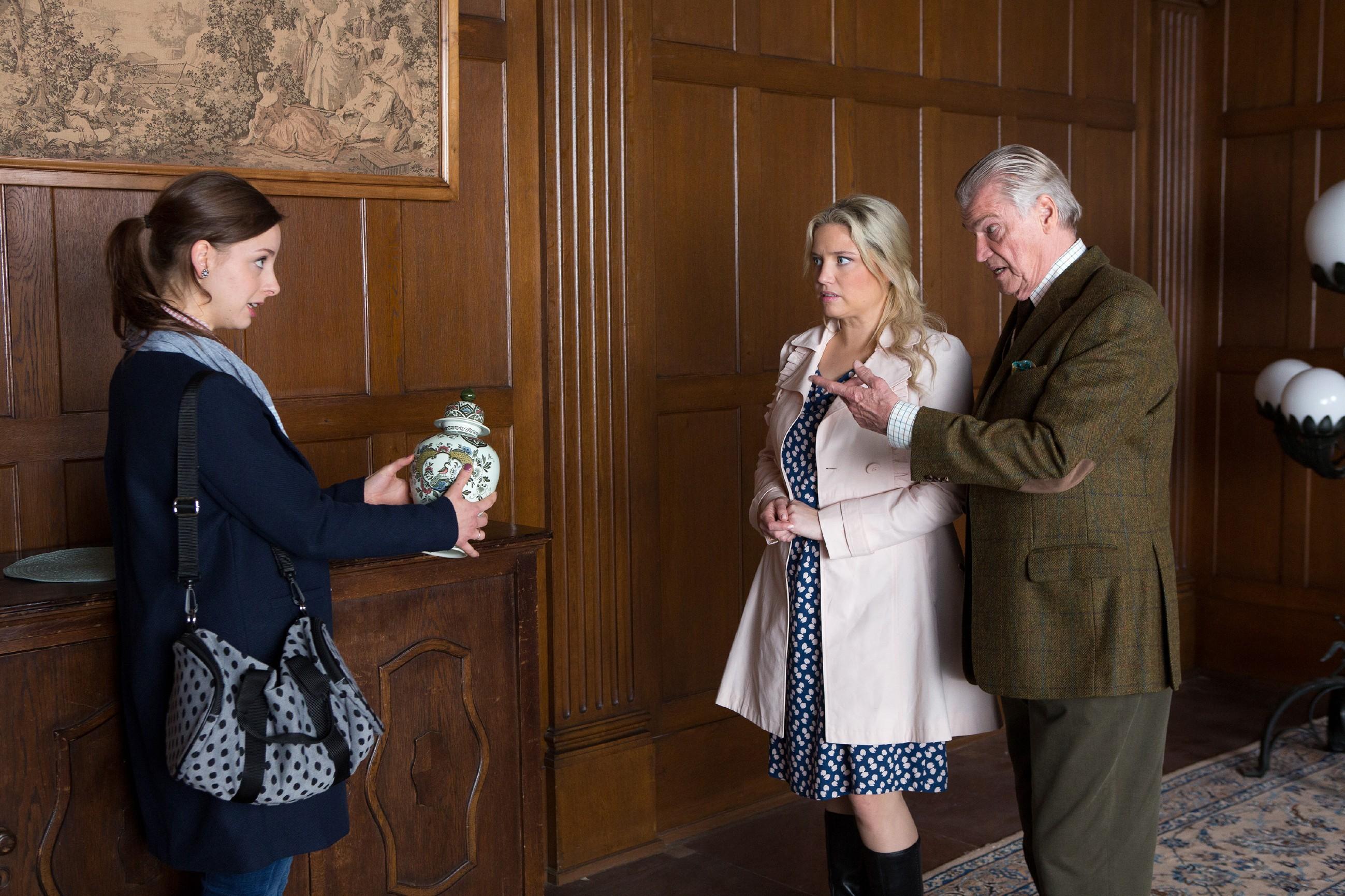 Helmut (Jochen Busse) erklärt Dagmar (Caroline Maria Frier, M.) und Nina (Amelie Plaas-Link), dass sich in der Urne auf dem Sideboard sein Bruder befindet.