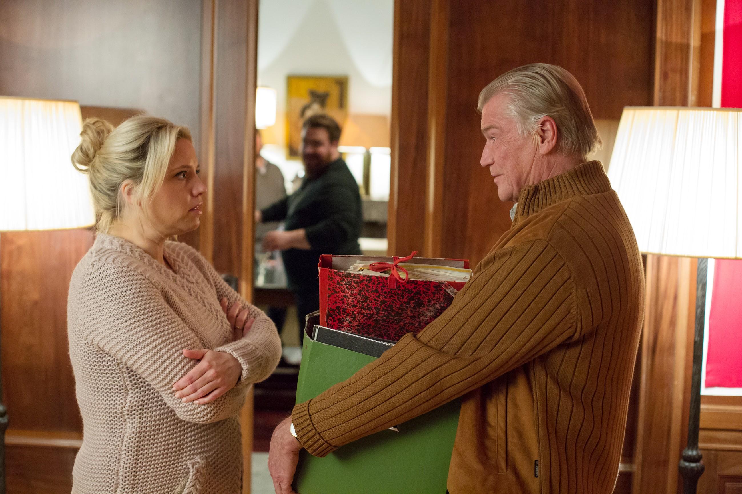 """Helmut (Jochen Busse) findet den roten Ordner und weist Dagmar (Caroline Maria Frier) auf eine """"rosige"""" Zukunft hin."""