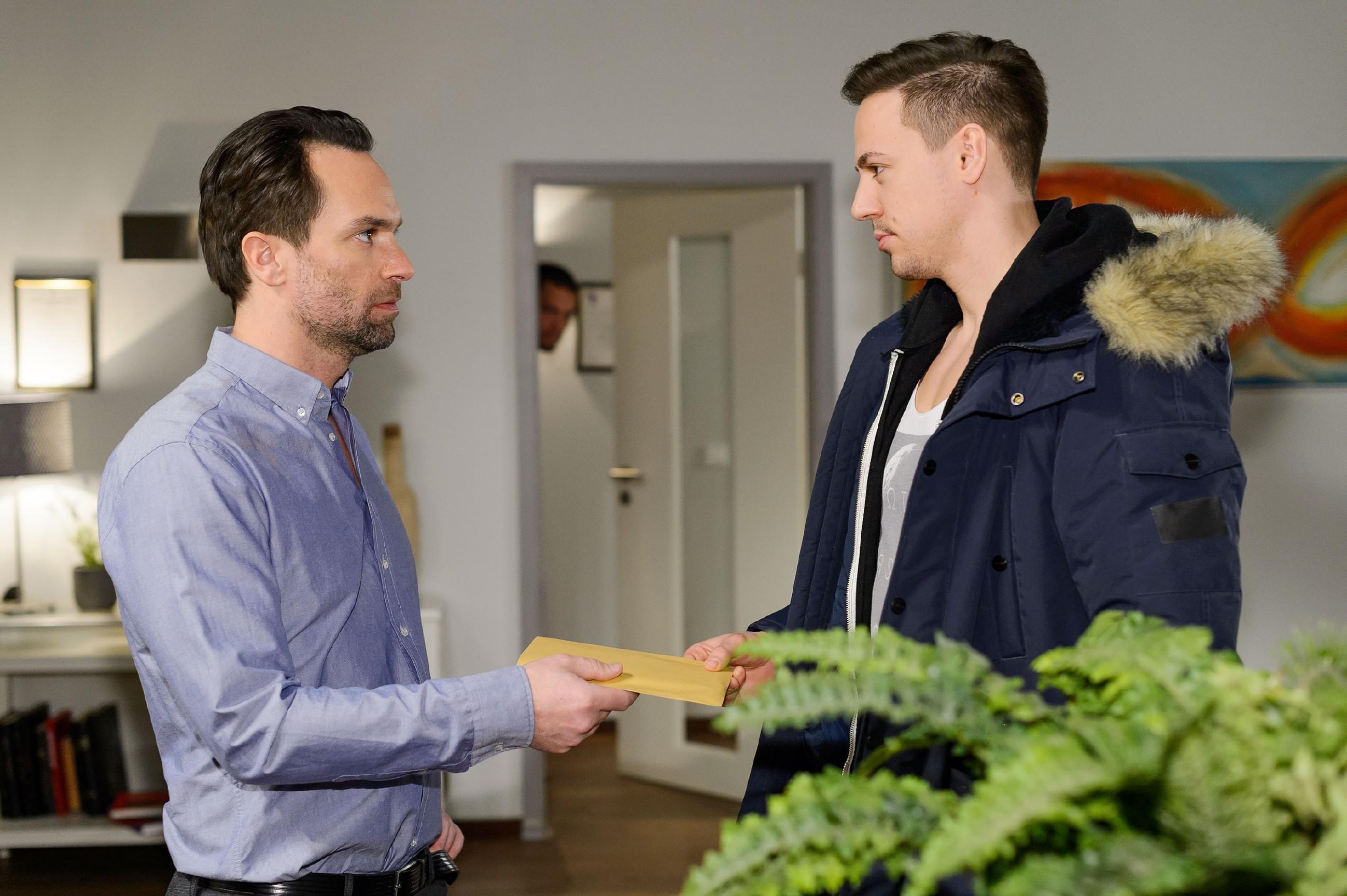 Thomas (Daniel Brockhaus, l.) nimmt von einem Kurier (Komparse) Leos (Julian Bayer, hinten) gefälschten Pass in Empfang. (Quelle: RTL / Willi Weber)