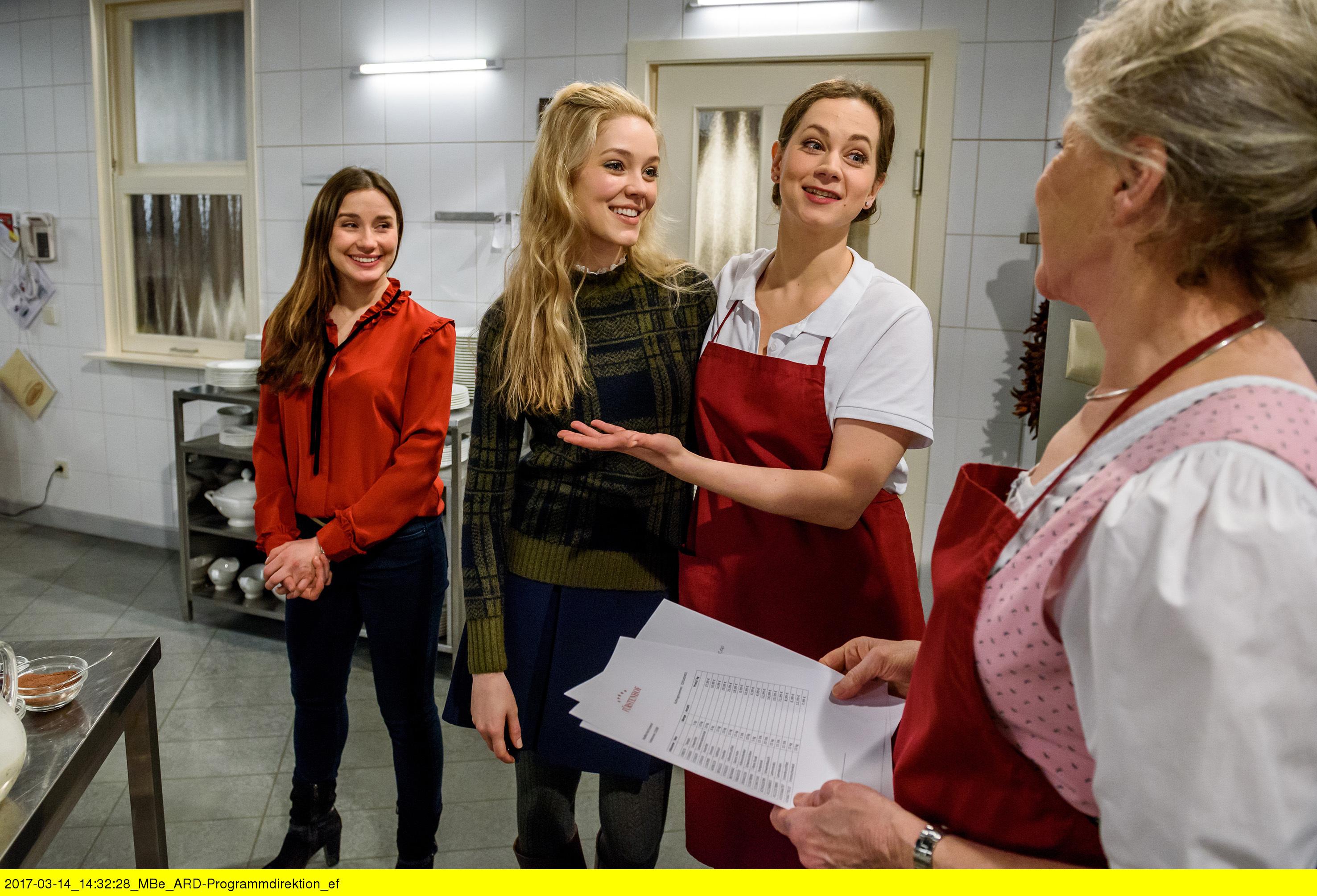 ARD STURM DER LIEBE FOLGE 2677, am Freitag (28.04.17) um 15:10 Uhr im ERSTEN. Clara (Jeannine Wacker, l.) platzt mit Ella (Victoria Reich, 2.v.l.) in die Küche und überascht Tina (Christin Balogh, 3.v.l.), die sich gerade mit Hildegard (Antje Hagen, r.) unterhält. (Quelle: ARD/Christof Anrold)
