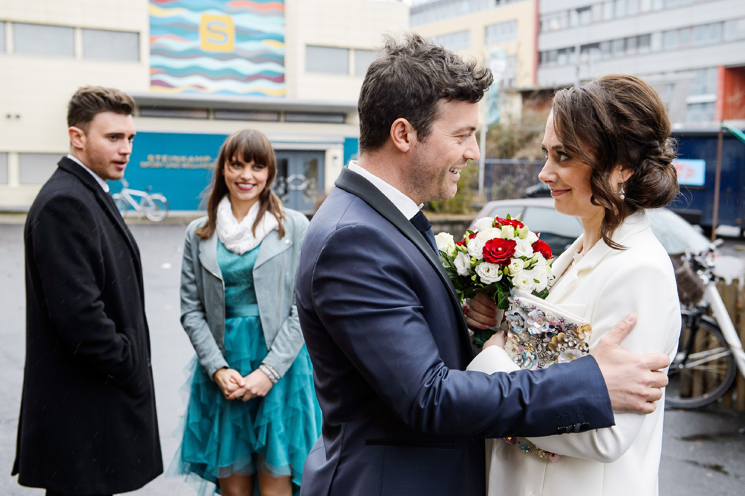 Während (v.l.) Ronny (Bela Klentze, l.) und Michelle (Franziska Benz) auf das Brautpaar warten, rührt Ben (Jörg Rohde) seine Carmen (Heike Warmuth) mit einer Überraschung. Daraufhin ist es Carmen unmöglich, ihm länger etwas vorzumachen...