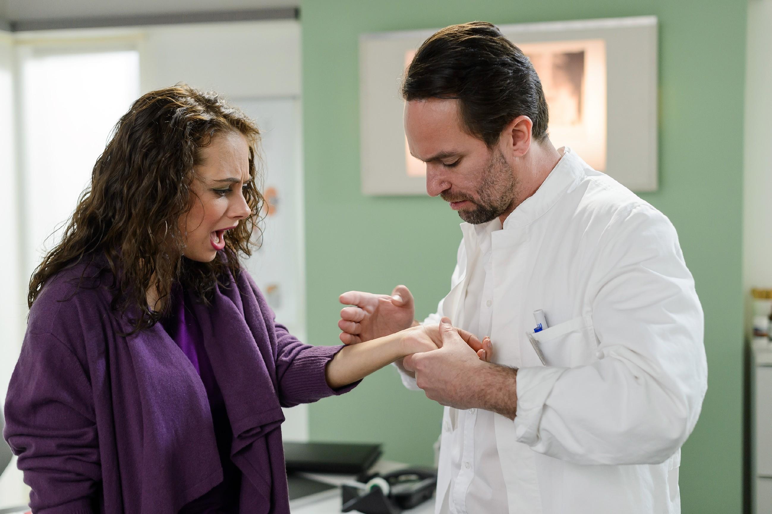 Carmen (Heike Warmuth) lässt sich nach ihrem Unfall von Thomas (Daniel Brockhaus) untersuchen.
