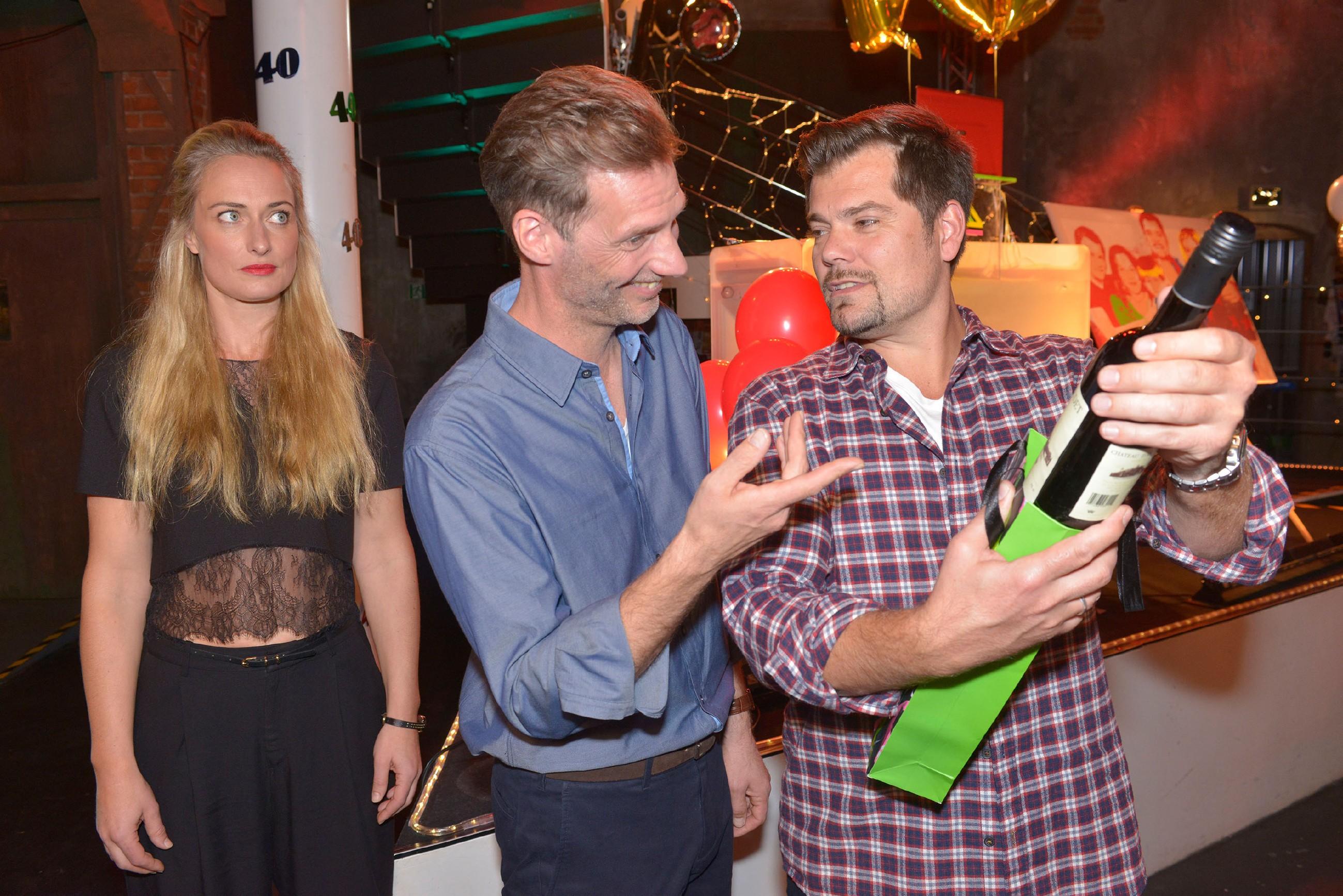 Maren (Eva Mona Rodekirchen) beobachtet genervt, wie Alexander (Celmens Löhr, M.) Leon (Daniel Fehlow) zu dessen 40. Geburtstag gratuliert. (Quelle: RTL / Rolf Baumgartner)