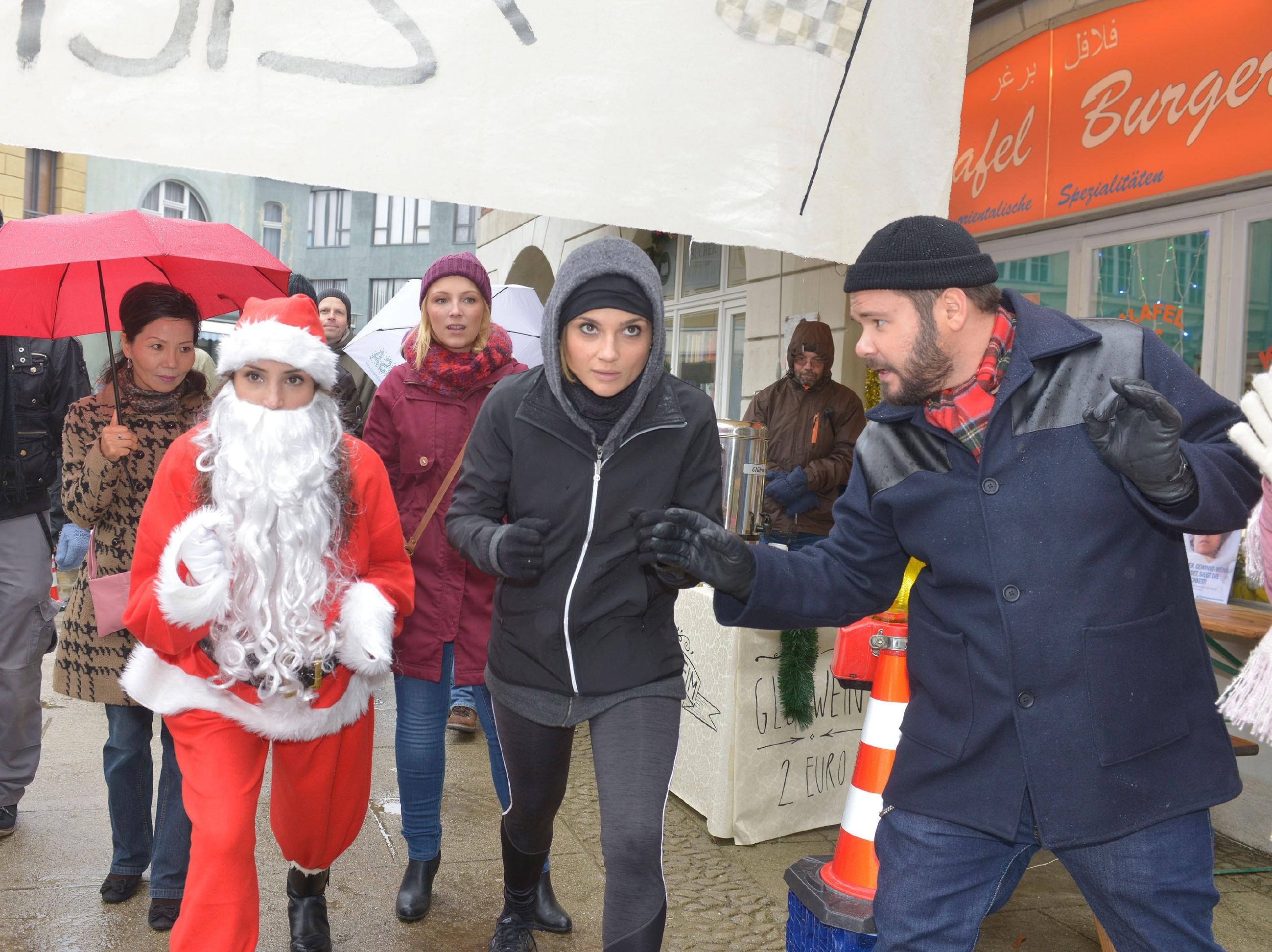 Tuner (Thomas Drechsel, r.) startet das Wettrennen zwischen Anni (Linda Marlen Runge, M.) und Ayla (Nadine Menz, l.) im Weihnachtsmannkostüm, aus dem Lilly (Iris Mareike Steen) einen Spendenlauf für ihre Sozialstation gemacht hat. (Quelle: RTL / Rolf Baumgartner)