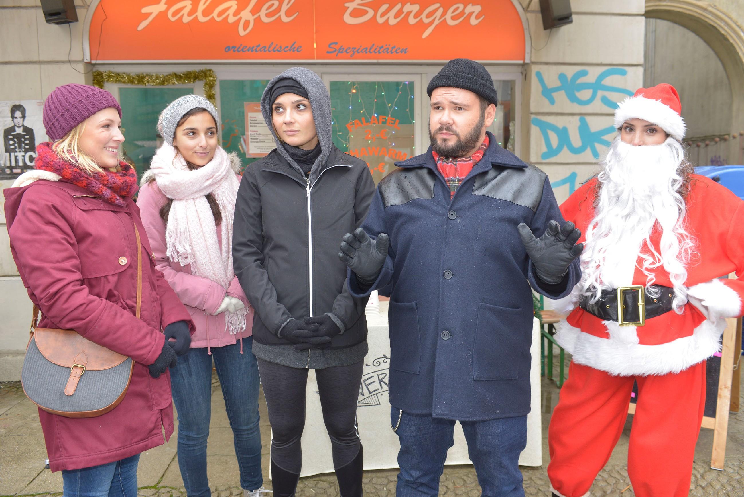 Lilly (Iris Mareike Steen, l.), Selma (Rona Özkan, 2.v.l.) und Tuner (Thomas Drechsel) sind gespannt, wie der Wettlauf zwischen Anni (Linda Marlen Runge) und Ayla (Nadine Menz) im Weihnachtsmannkostüm ausgehen wird. (Quelle: RTL / Rolf Baumgartner)