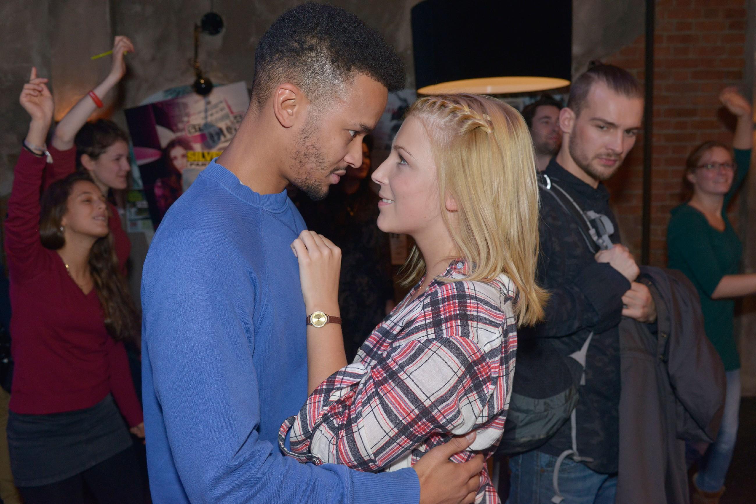 Lilly (Iris Mareike Steen) ist fassungslos vor Glück, als während des Konzerts plötzlich Amar (Thando Walbaum, l.) vor ihr steht. Chris (Eric Stehfest) hingegen hält sich bei dem Wiedersehen rücksichtsvoll im Hintergrund. (Quelle: RTL / Rolf Baumgartner)