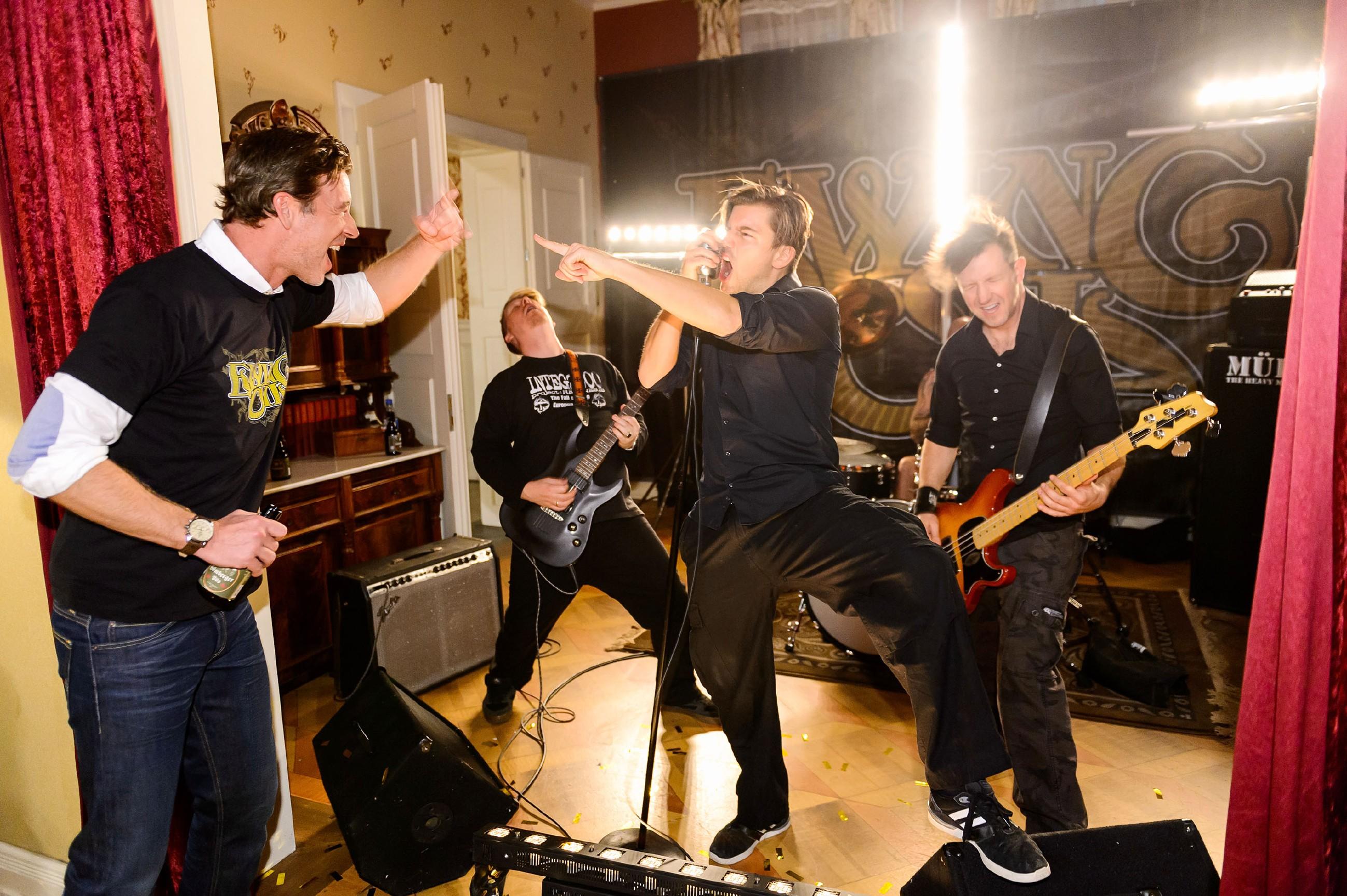 """Christoph (Lars Korten) feiert ausgelassen seinen Geburtstag und rockt gemeinsam mit der Heavy-Metal-Band """"Ewing Oil"""" (Komparsen), deren Auftritt Vanessa für ihn organisiert hat. (Quelle: RTL / Willi Weber)"""