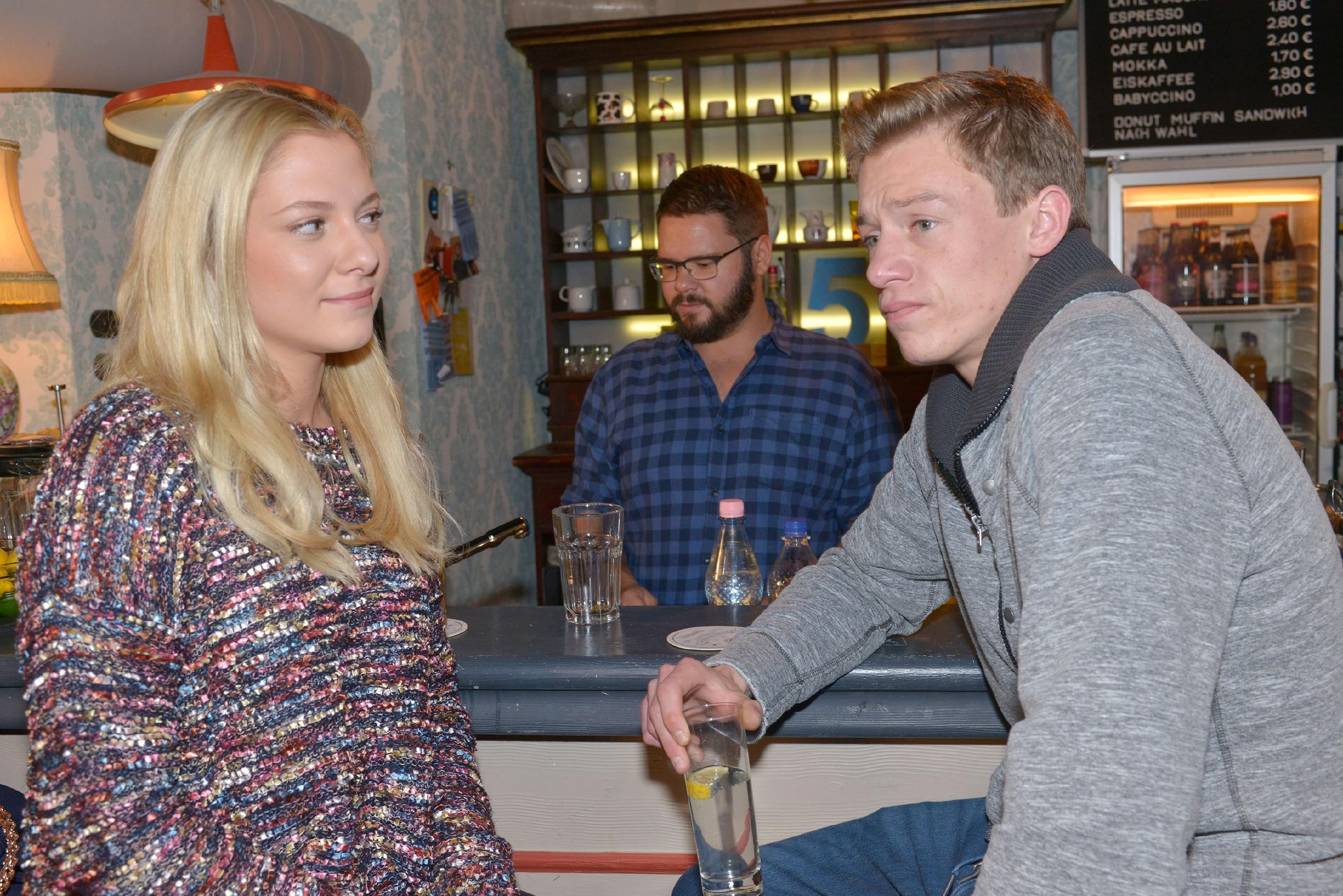 Vince (Vincent Krüger, r.) sitzt mit Sunny (Valentina Pahde) bei Tuner (Thomas Drechsel) an der Bar und erklärt ihr, dass er von seiner Geschäftsidee überzeugt ist.