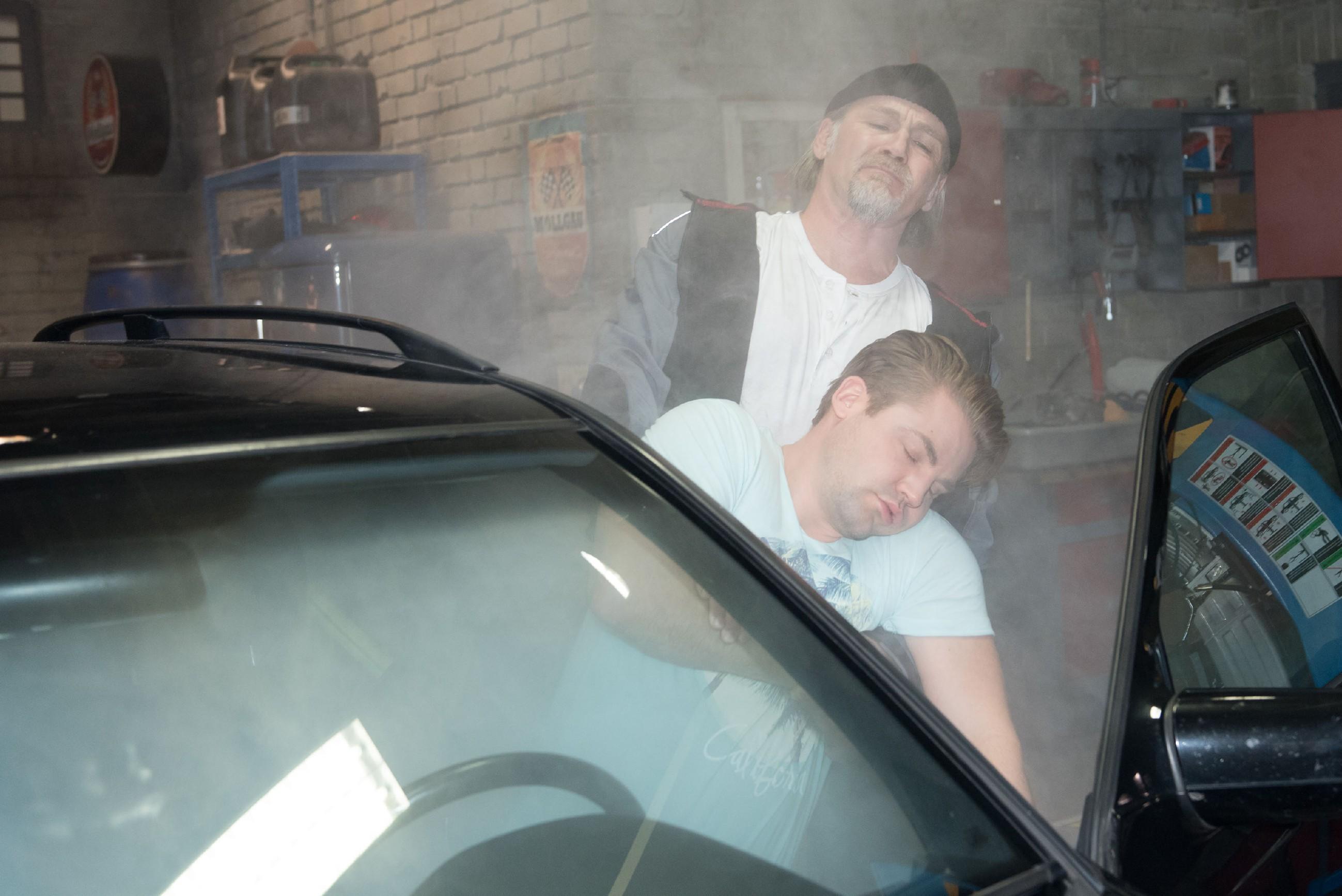 Robert (Luca Maric) findet schockiert den reglosen Bambi (Benjamin Heinrich, vorne) und zieht ihn aus dem Auto. (Quelle: RTL / Stefan Behrens)